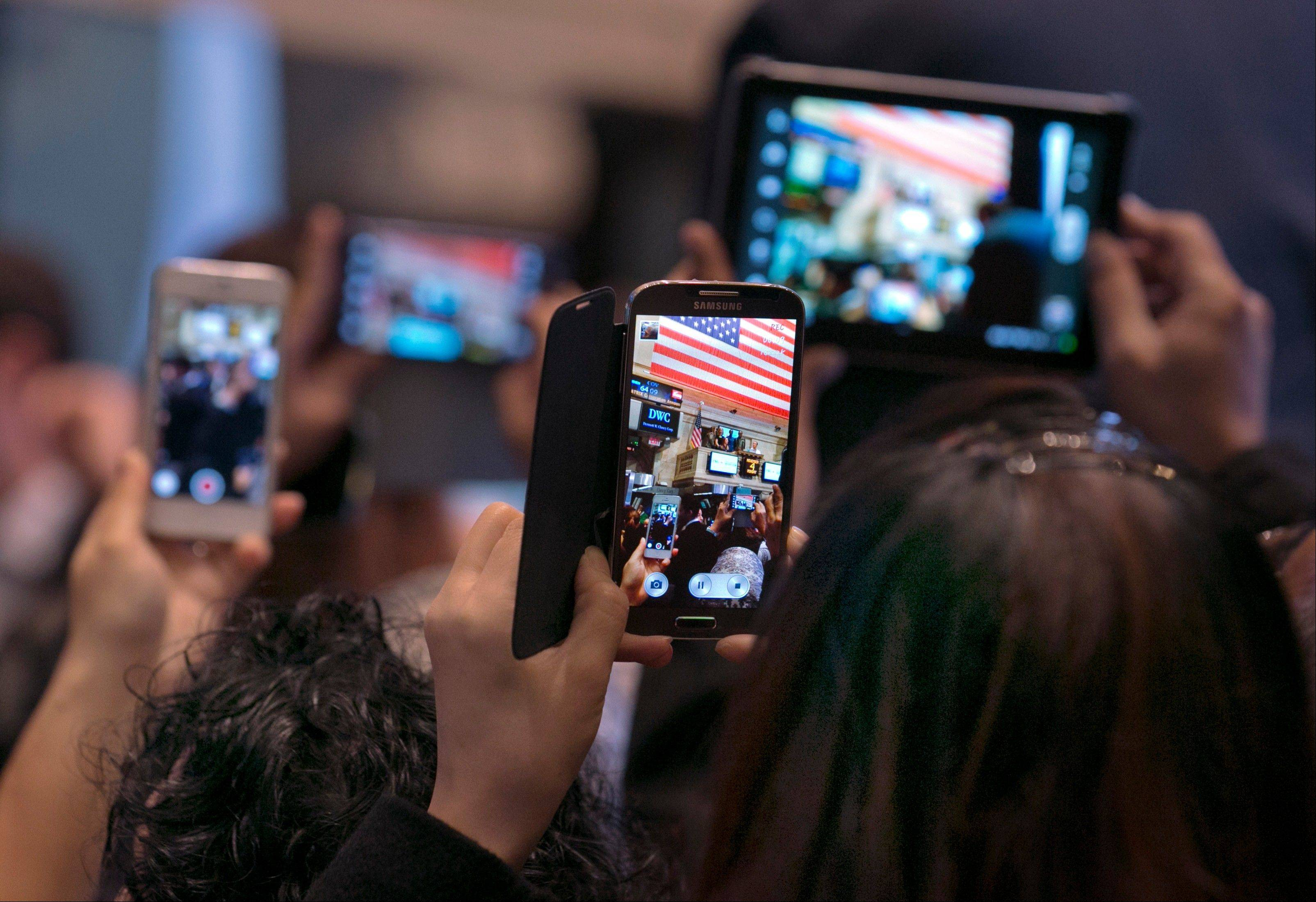 Visitors on the floor of the New York Stock Exchange use their smartphones and tablet devices to photograph the opening bell ceremonies Monday. Twitter's confidence appears to be increasing ahead of its initial public offering set for later this week at the NYSE, as 7-year-old short messaging service on Monday boosted the price range for the IPO.