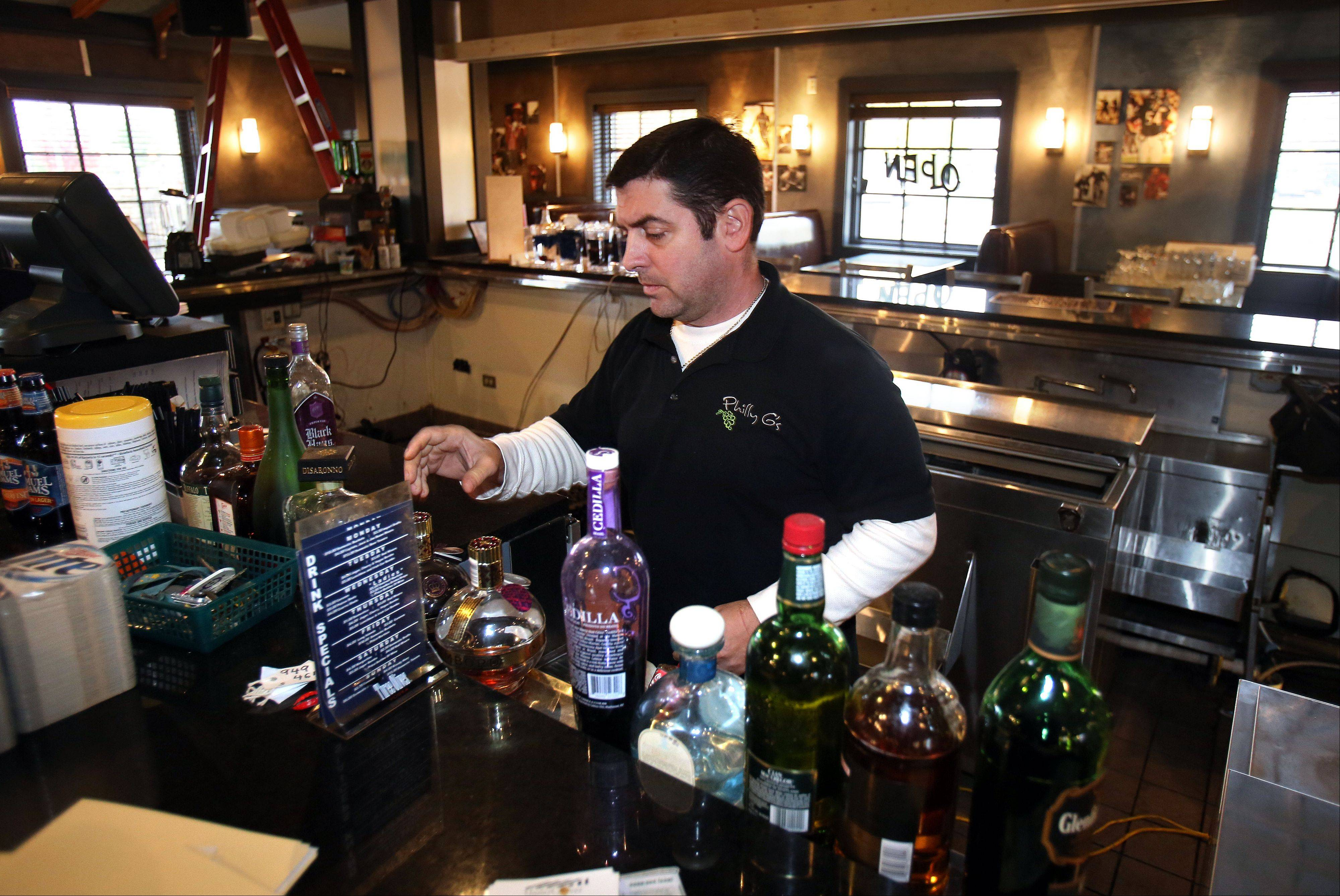 Phil Gilardi sorts through liquor bottles at the former Blue 60 in Mundelein. Gilardi has bought the establishment and will be reopening it as Tavern on 60.