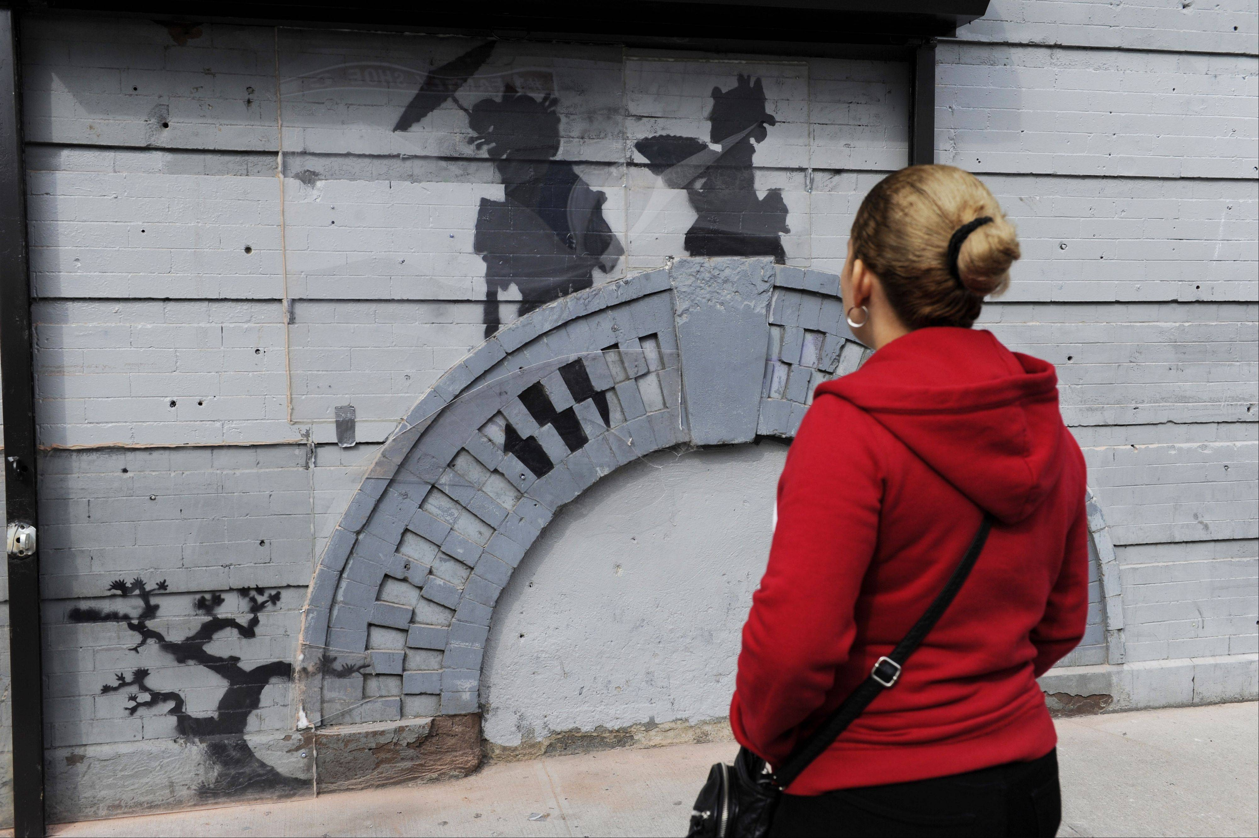 A woman looks at a work by British graffiti artist Banksy in New York's Brooklyn Borough. The secretive street artist ended his self-announced monthlong residency in New York with a final piece of graffiti, a $615,000 painting donated to charity.