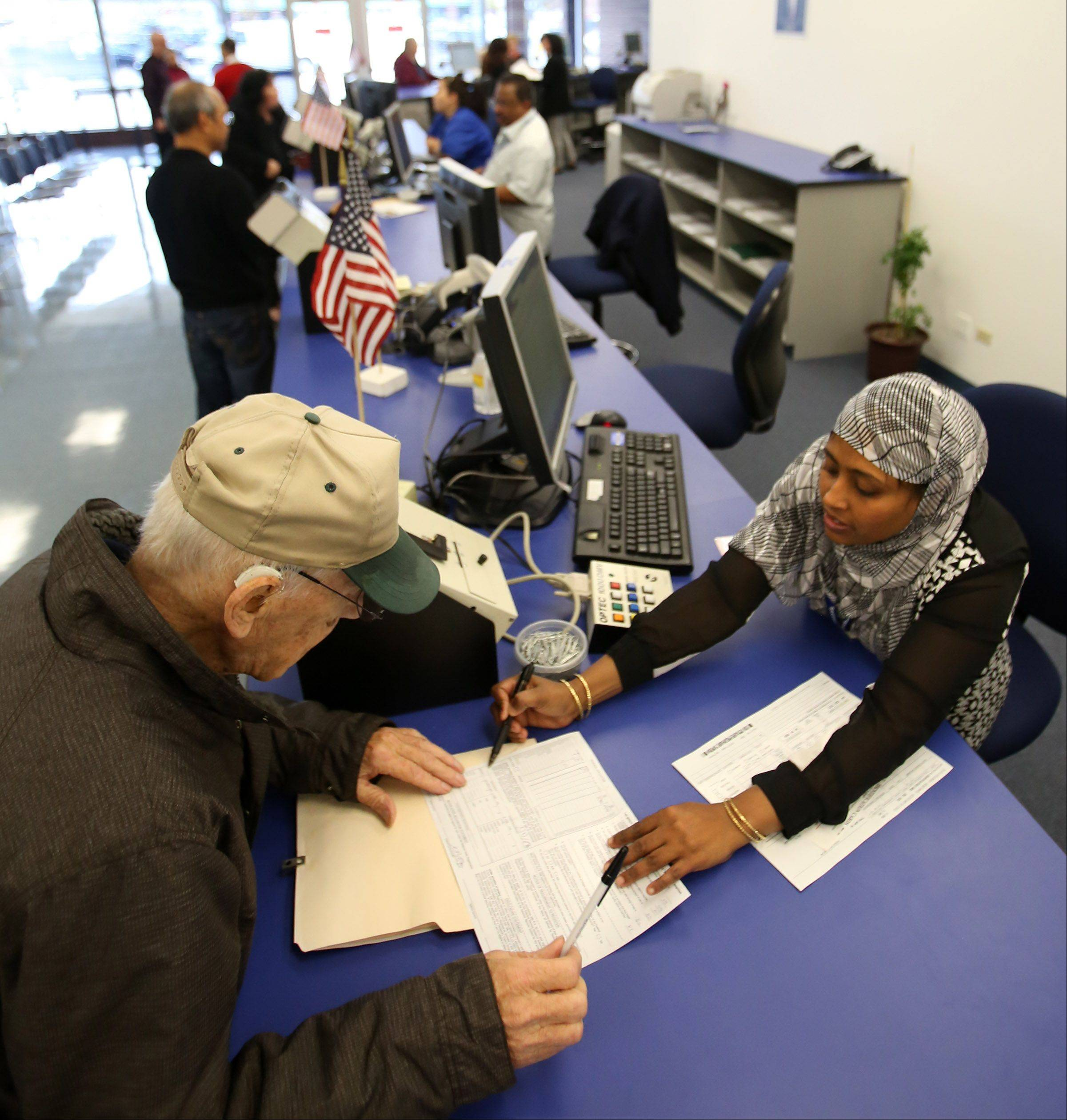 Robert Sperling of Des Plaines renews his drivers license Tuesday with Secretary of State employee Nahida Nasrin on the opening day of a new driver services facility in Des Plaines. Sperling said he lives only a mile away and didn't have to wait in line at all.