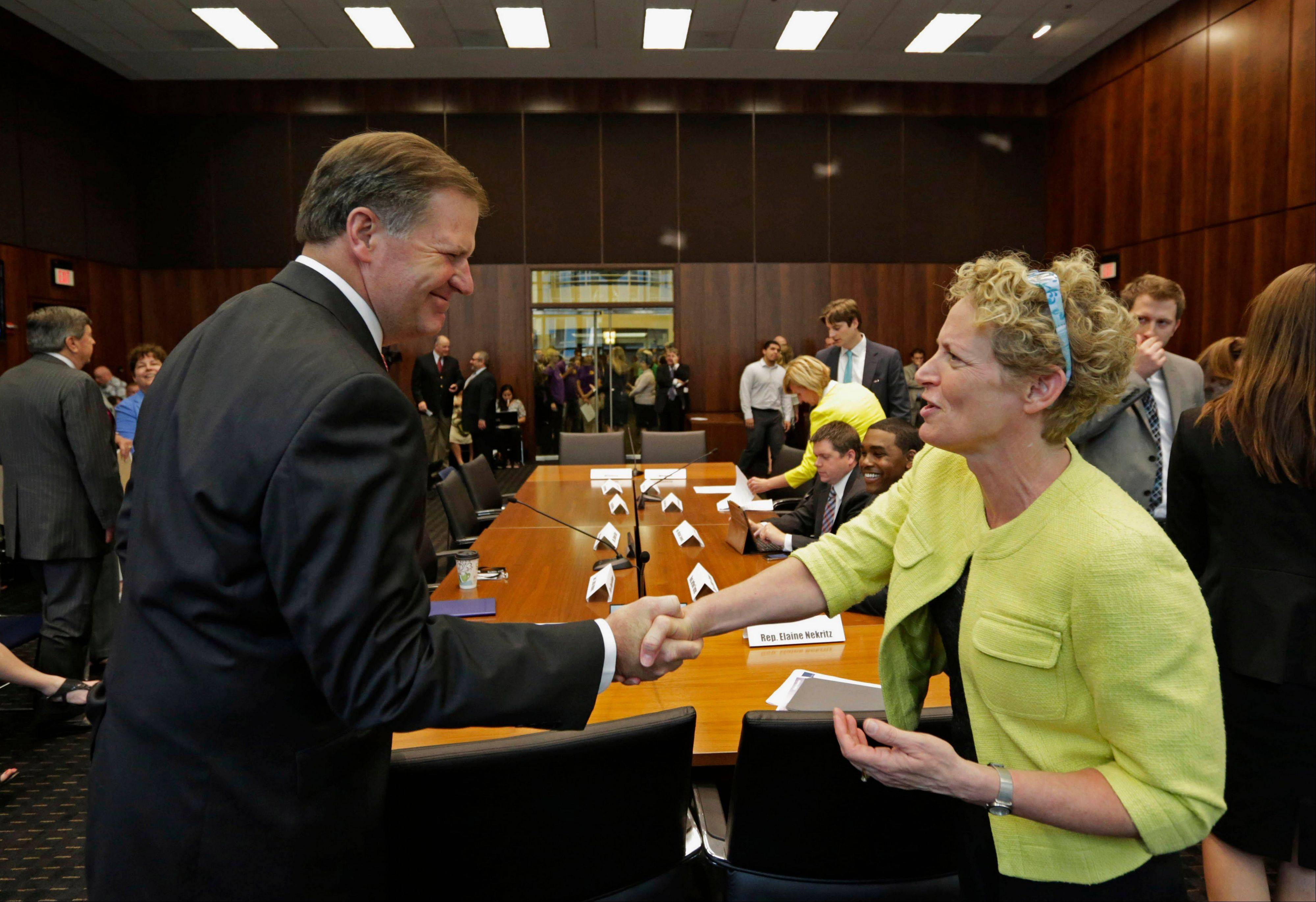 In this June 27, 2013 file photo, Illinois state Sen. Bill Brady, left, and state Rep. Elaine Nekritz of Northbrook, shake hands before apublic pension hearing in Chicago. Lawmakers say they are making progress on a deal to solve Illinoisí $97 billion pension crisis, but are not confident there will be a vote as the annual fall legislative session enters its final days beginning Tuesday.