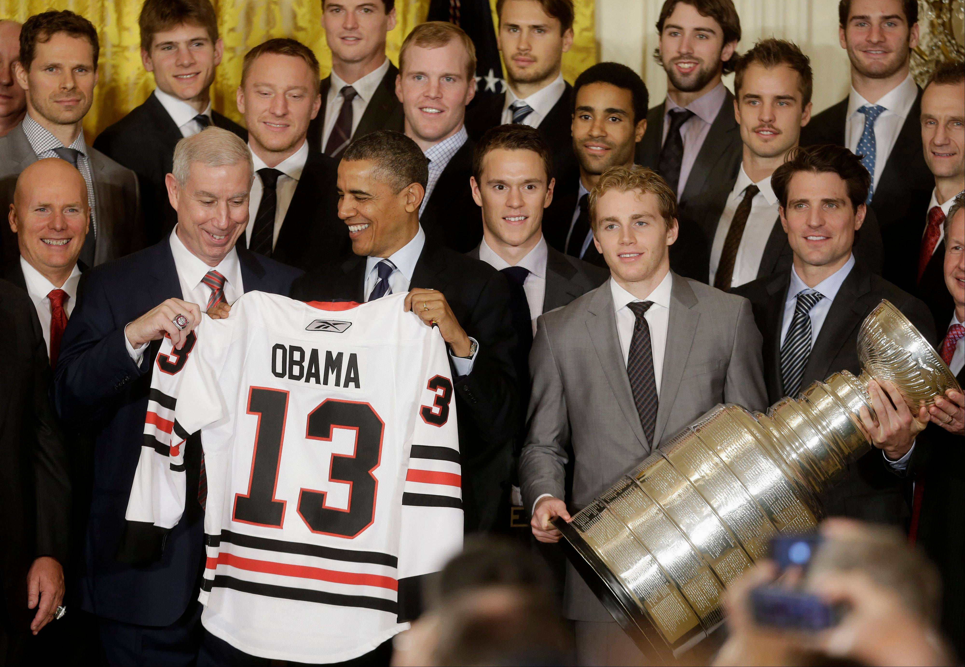 Chicago Blackhawks President and CEO John McDonough, left, presents President Barack Obama with a Chicago Blackhawks hockey jersey during a ceremony in the East Room of the White House Monday to honor the NHL 2013 Stanley Cup champions. Team captain Jonathan Toews is at center, and Patrick Kane and Patrick Sharp, right, hold the Stanley Cup.