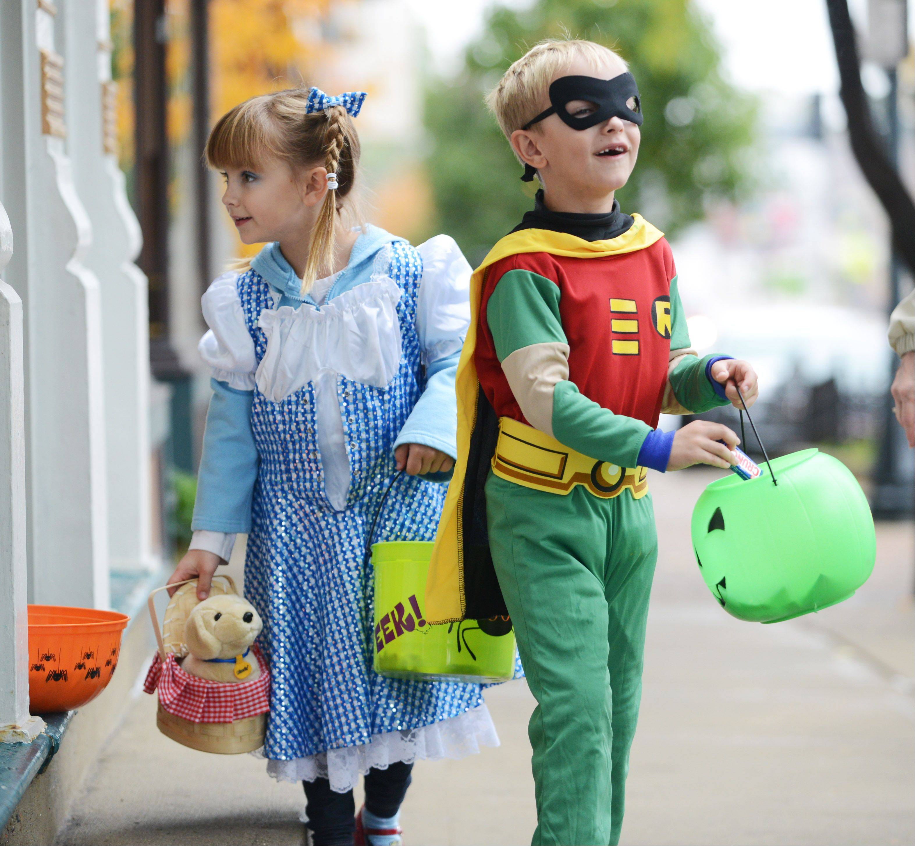 Seven-year-old Bailey Truitt, left, dressed as Wizard of Oz character Dorothy while her twin brother, Lucas, both of Grayslake, dressed as Robin during the MainStreet Libertyville Trick or Treat event Friday.