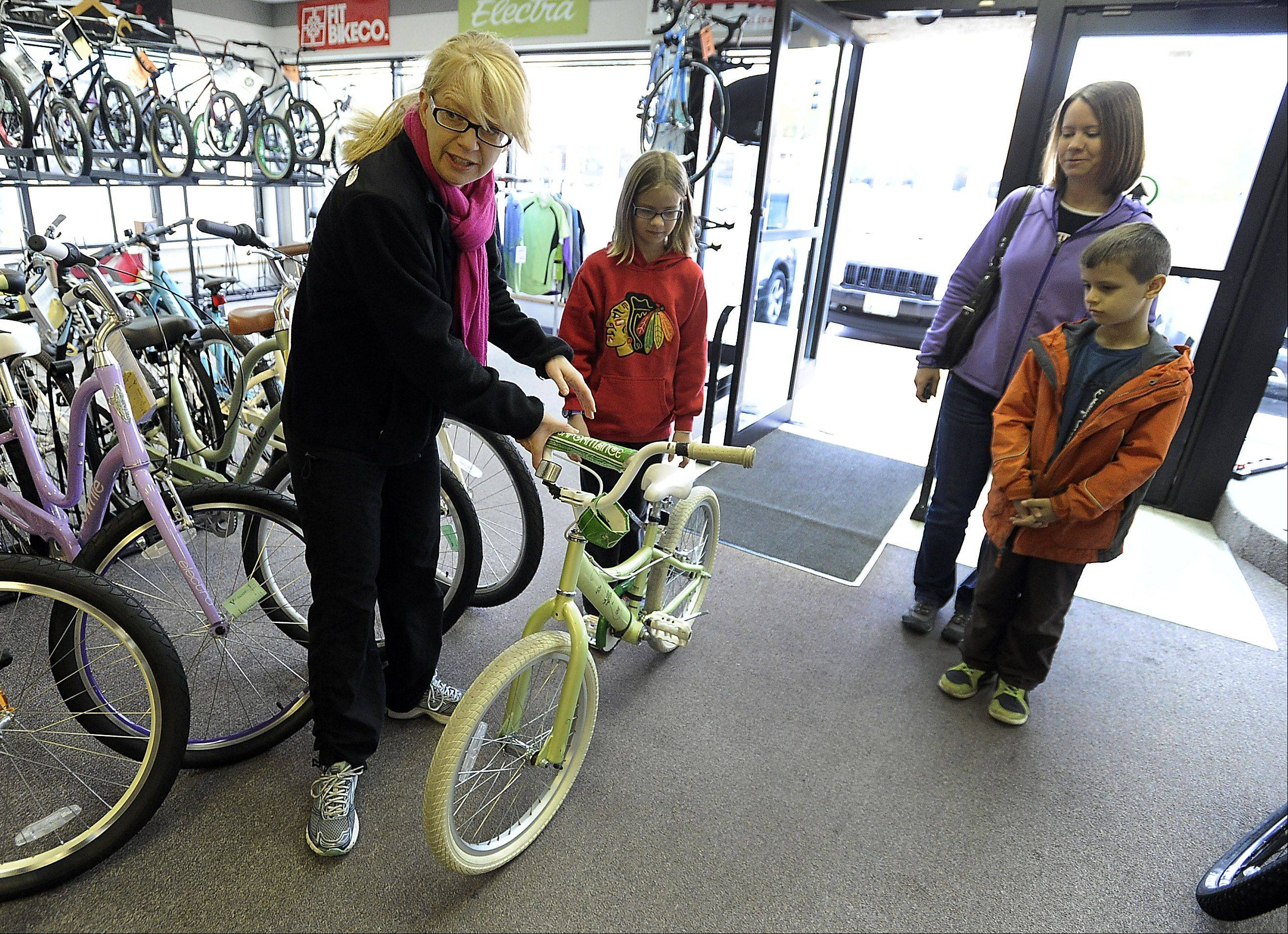 Marla Bradley of the Pedal Power Bike Drive in Palatine, takes a bike from Karolyn Hilquist, 10, which she received as a Christmas gift many years ago, as her mom, Beth, and brother Ben, 8, look on. The bikes were donated through Mike's Bike Shop on Saturday and will be passed along to the Chicago Public Schools as a reward for good grades.