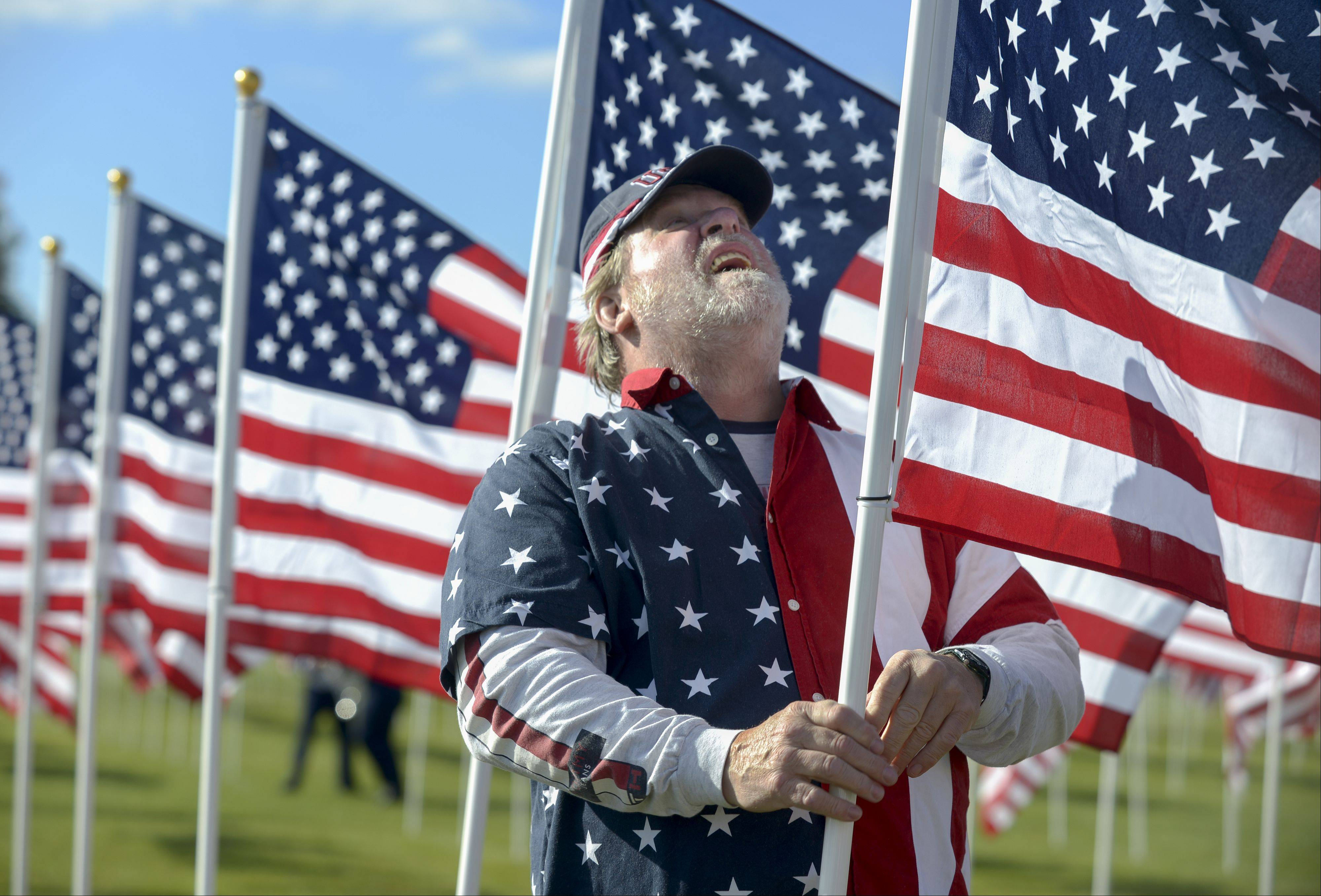 Marine Corp, Vietnam veteran Jake Horn, of Sugar Grove, adjusts one of the over 2,000 American flags on Aurora Healing Field at West Aurora High School Sunday. Horn was part of a group of volunteers who helped install the flags early Sunday morning.