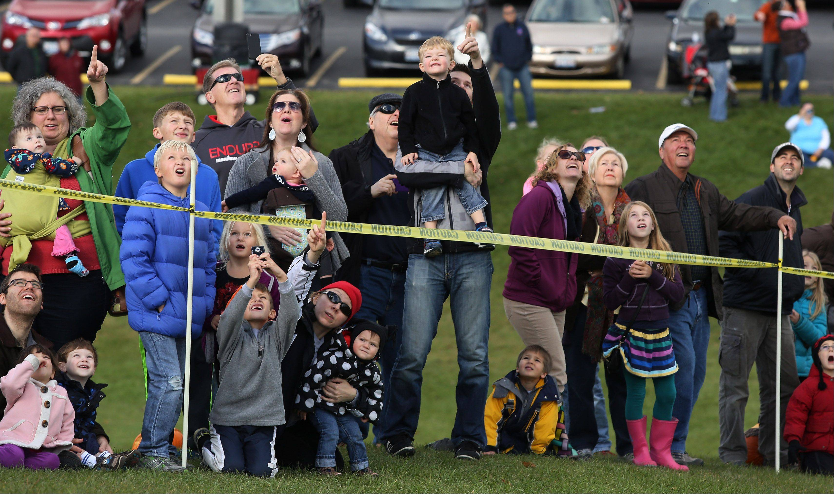 Spectators watch the launch of another pumpkin by Big Red, the catapult, during Mundelein's 6th Annual Pumpkin Drop Sunday at Keith Mione Community Park. Families brought their Halloween pumpkins to the event where they were bashed, rolled and flung with the catapult.