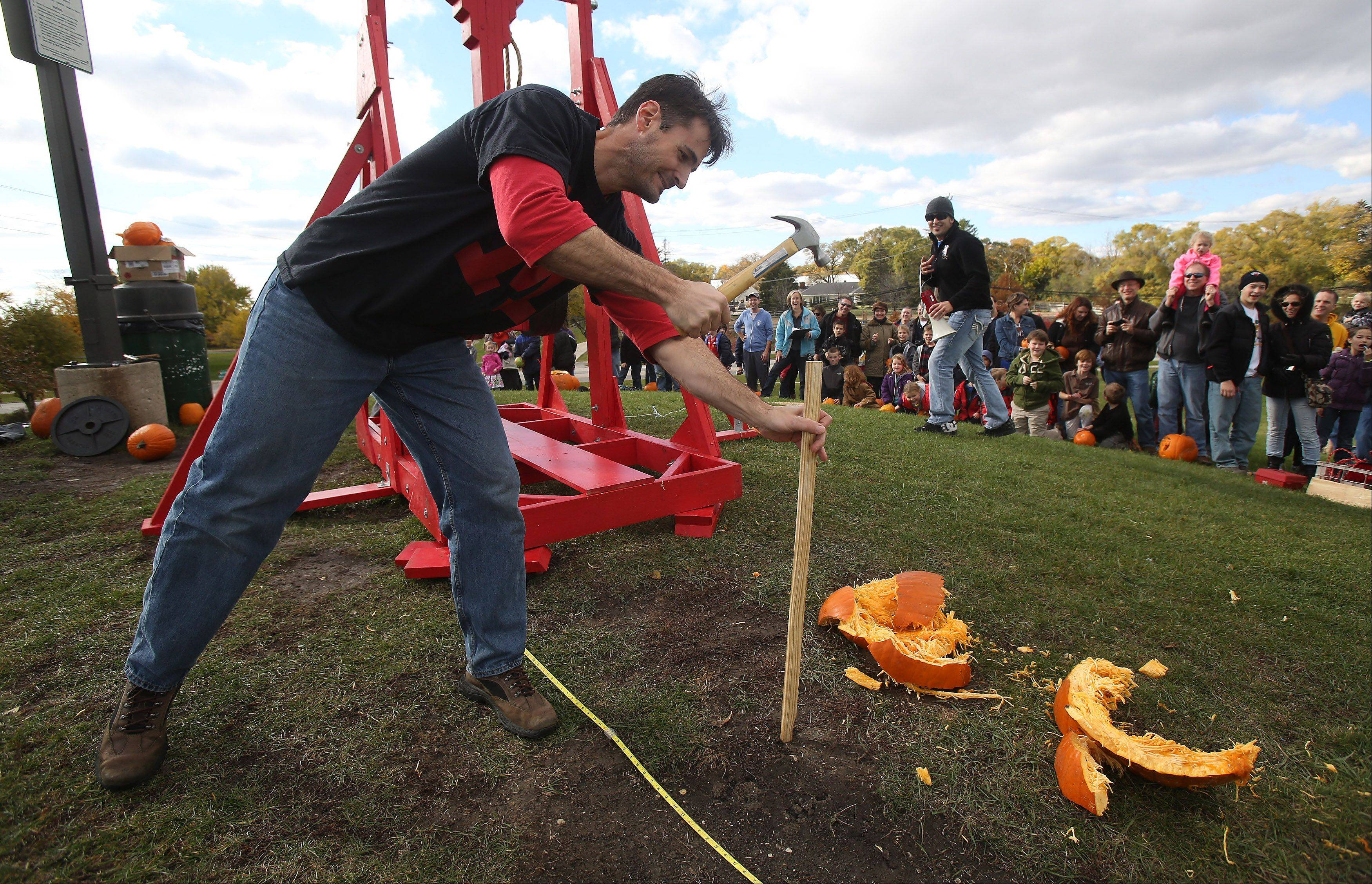 Mundelein High School physics teacher Mike Hickey marks the landing of the first pumpkin a couple of feet from the catapult after it went straight up after its launch during Mundelein's 6th Annual Pumpkin Drop Sunday at Keith Mione Community Park. Families brought their Halloween pumpkins to the event where they were bashed, rolled and flung with a catapult. Big Red, the catapult, designed and built by Mundelein High School students, was the star of the event.