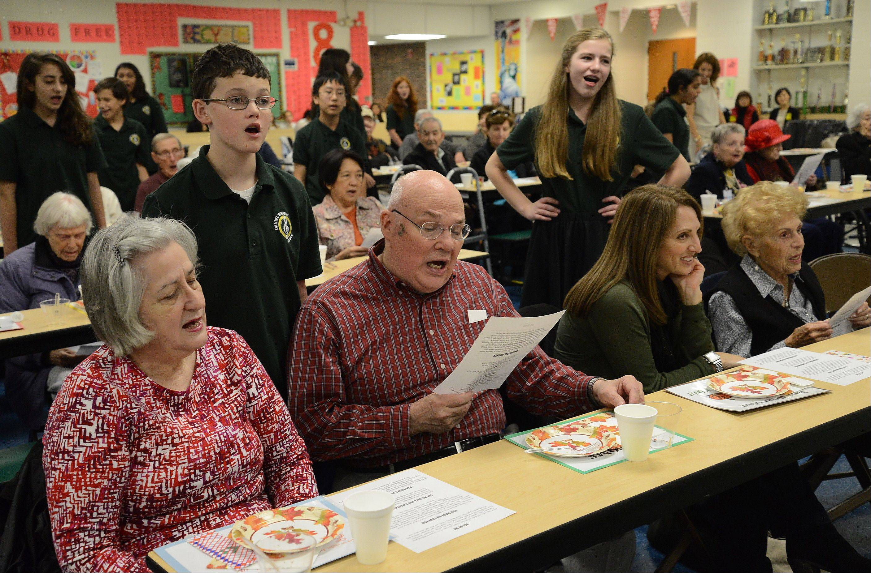 Jonathan Embree, left, joins his grand parents Tom and Connie Embree in a sing-a-long during Senior Citizens Day Tuesday at Daniel Wright Junior High in Lincolnshire.
