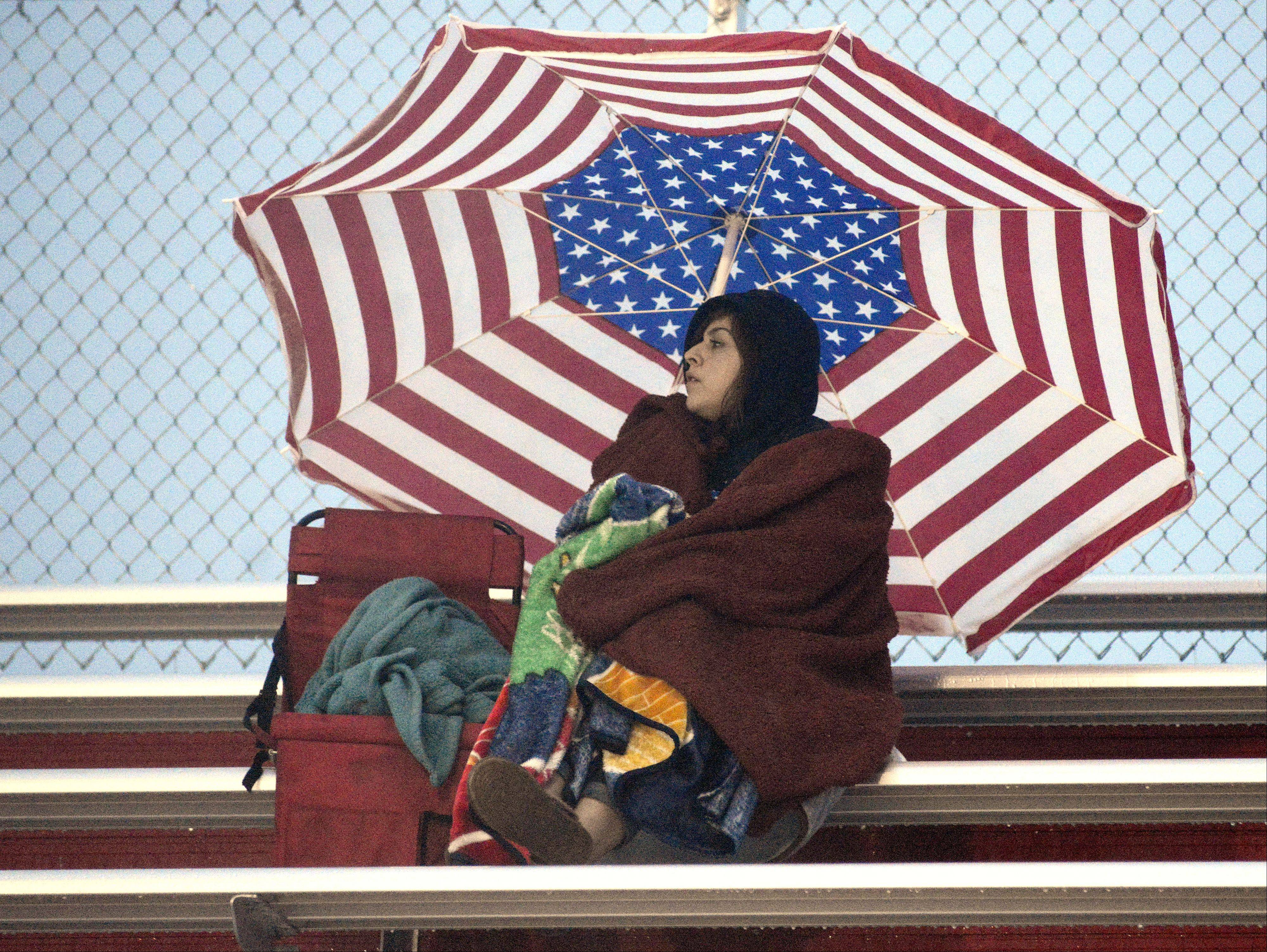 Jasmine Delgado, 17, of Elgin, huddles under a patio umbrella in the stands at Huntley High School during the Larkin vs. Hononegah boys soccer sectional semifinals on Wednesday. Delgado attended the game with Maria Alvarez, whose son, Freddy, plays for Larkin.