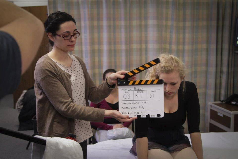 "NIU film student Margaret Balwierz holds the slate as student actresses Kaitlyn Finklestein and Lexi Langlois get ready for a hospital scene in the student film ""In Motion,"" which addresses the issue of campus sexual assault. NIU student filmmakers spent a year researching the prevalence of sexual assault on college campuses."