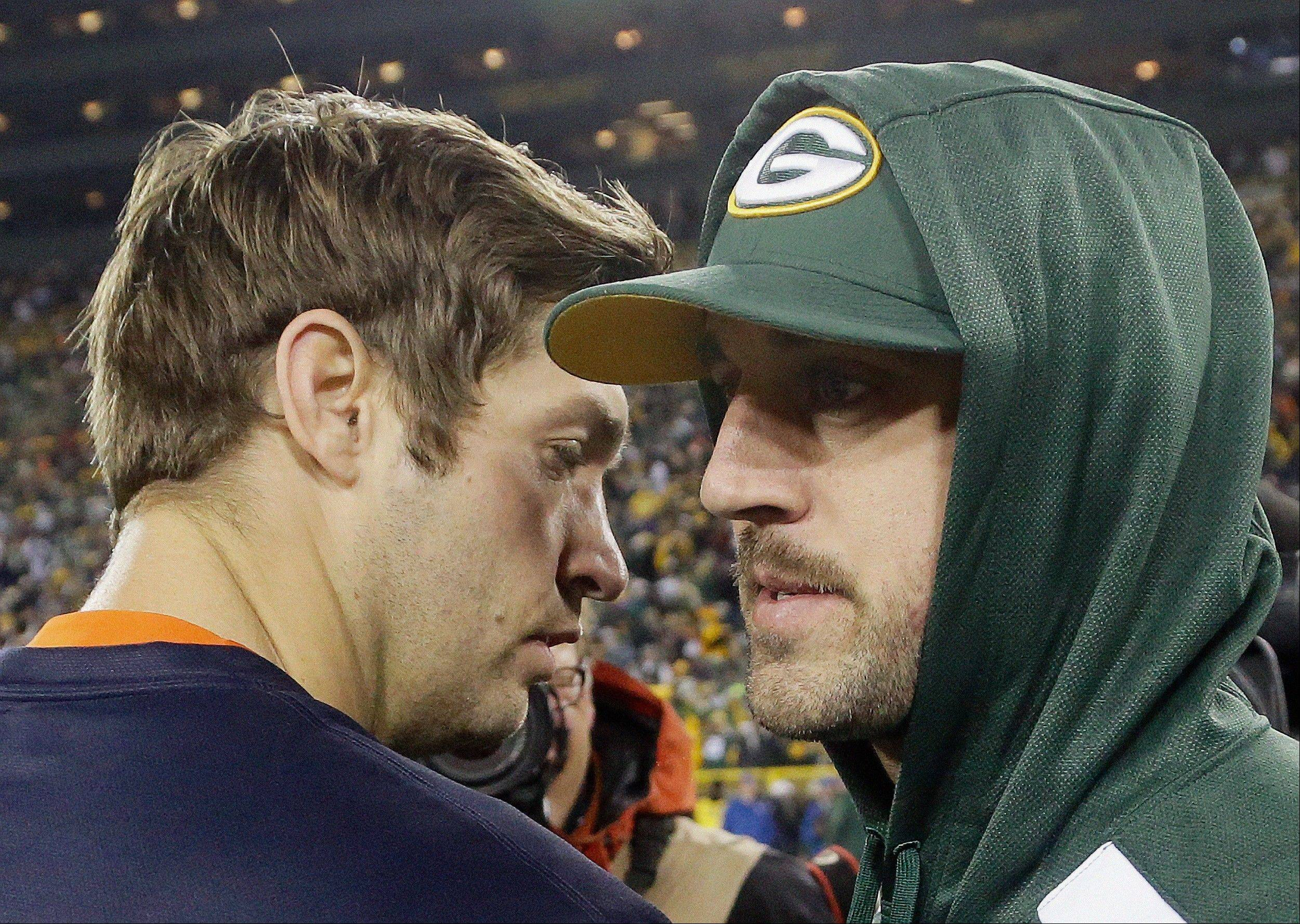 Green Bay Packers quarterback Aaron Rodgers, right, talks to the Bears' Jay Cutler after Monday's game at Lambeau Field. Both watched the game from the sidelines -- Rodgers suffered an injury in the first half.