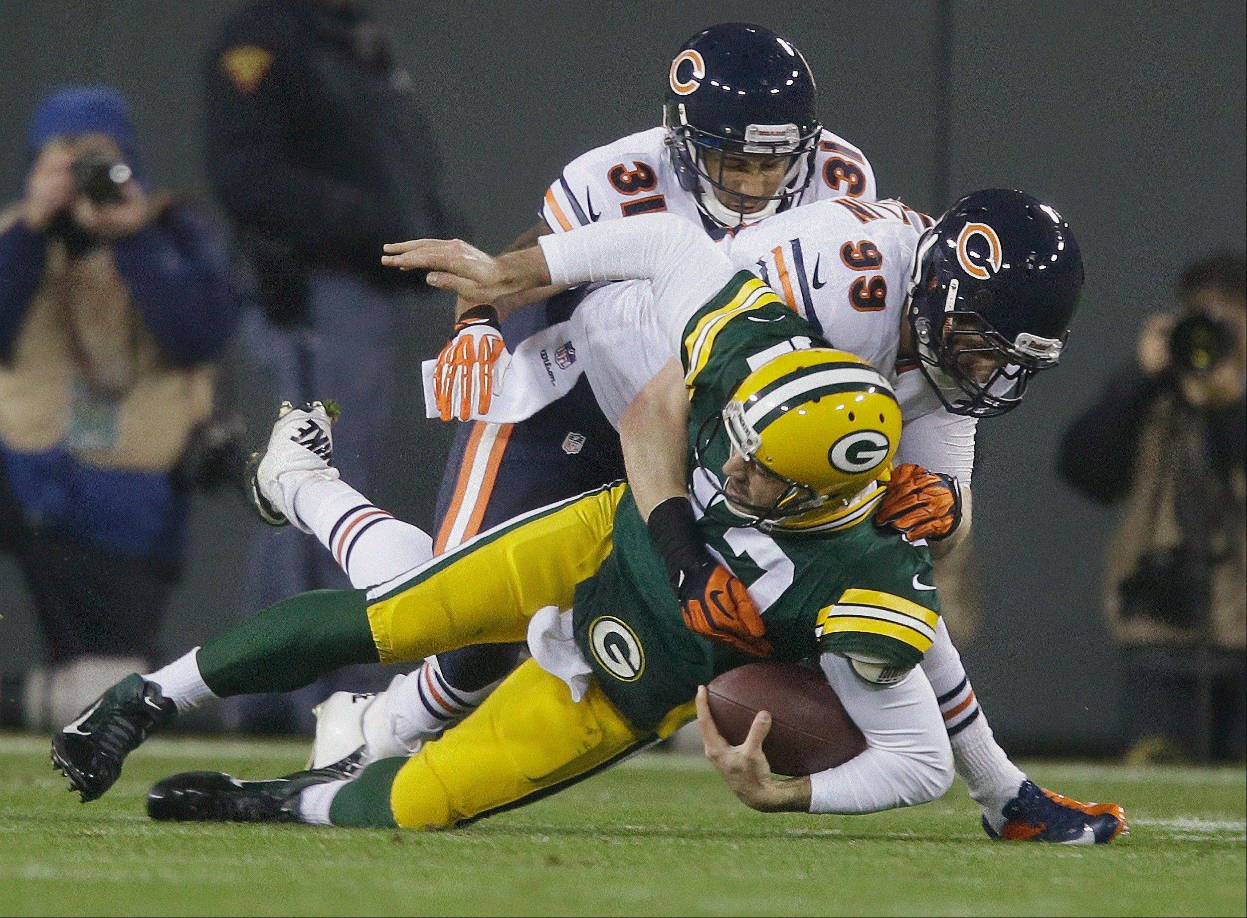 Green Bay Packers quarterback Aaron Rodgers is sacked by the Bears' Shea McClellin (99) and Isaiah Frey (31) during the first half.