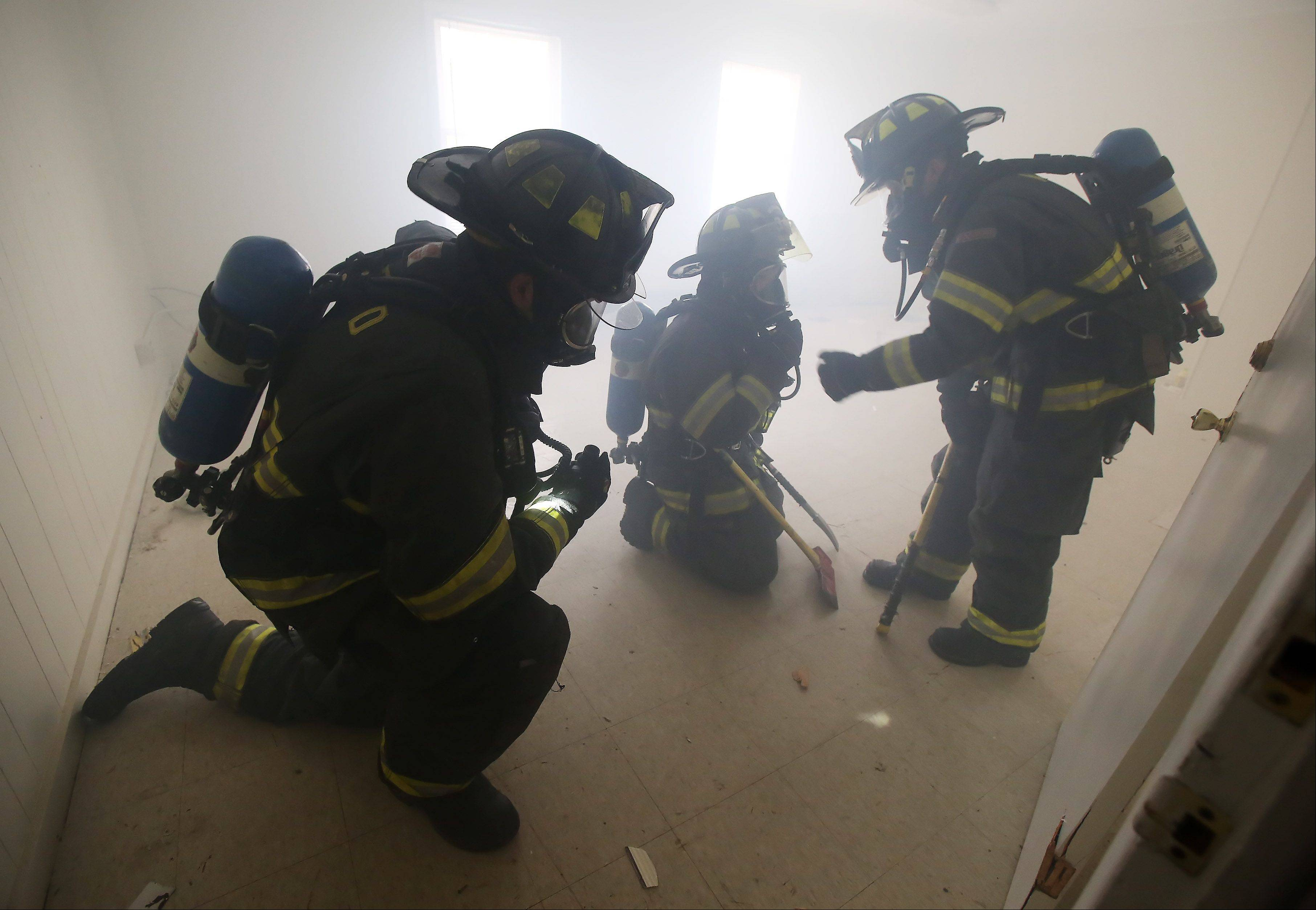 McHenry Township Fire Protection District firefighters Kevin Betke, left, Lexi Chancellor and Joe Studer participate in a training exercise Tuesday using the former Lakemoor village hall. The department will be conducting training in the building this week in advance of its demolition.