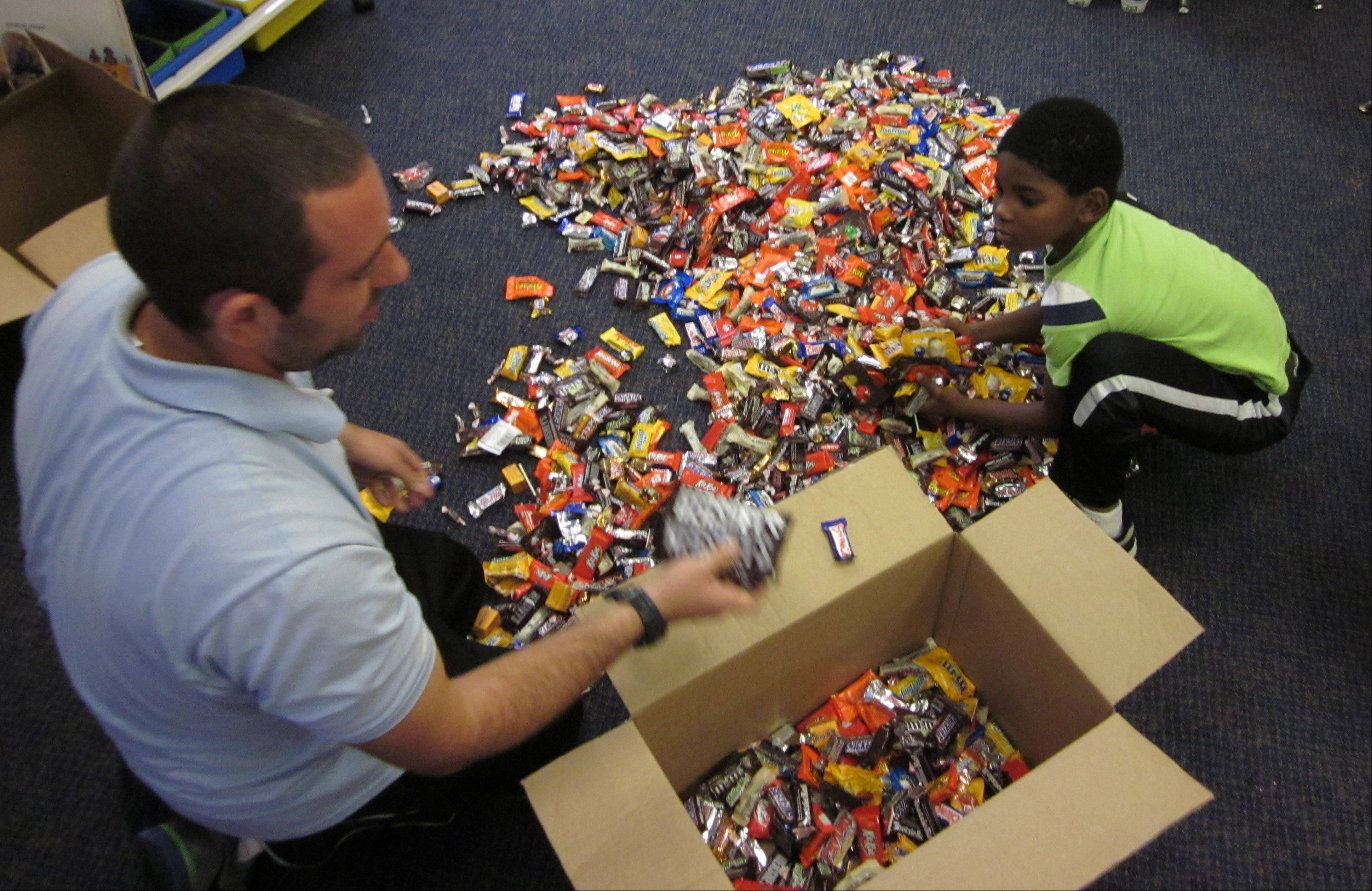Woodview School health/physical education teacher Steven Feldman, left, helped spur pupils into donating Halloween candy to troops at the Grayslake school. He receives assistance sorting candy Tuesday in first-grade teacher Jennifer Miller�s classroom.