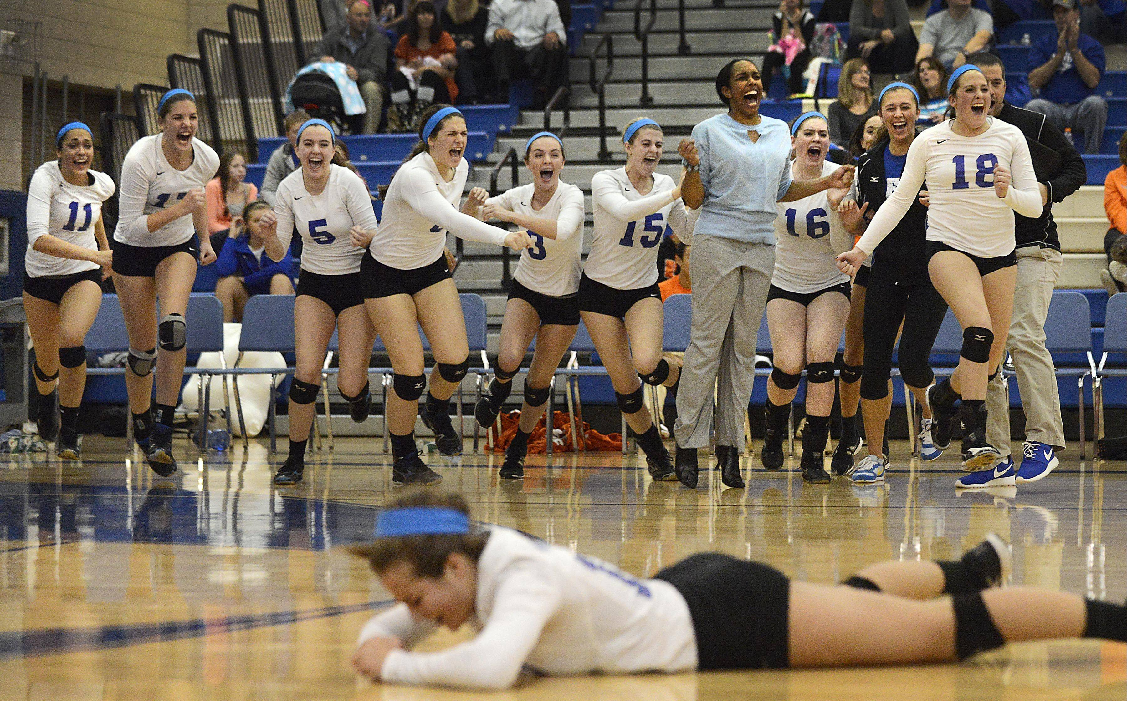 St. Charles North head coach Lindsey Hawkins leads the team in celebration off the bench as setter Sydney Wohlert collapses to the floor after the North Stars beat St. Charles East in two games Tuesday in the Class 4A sectional semifinal in Geneva.