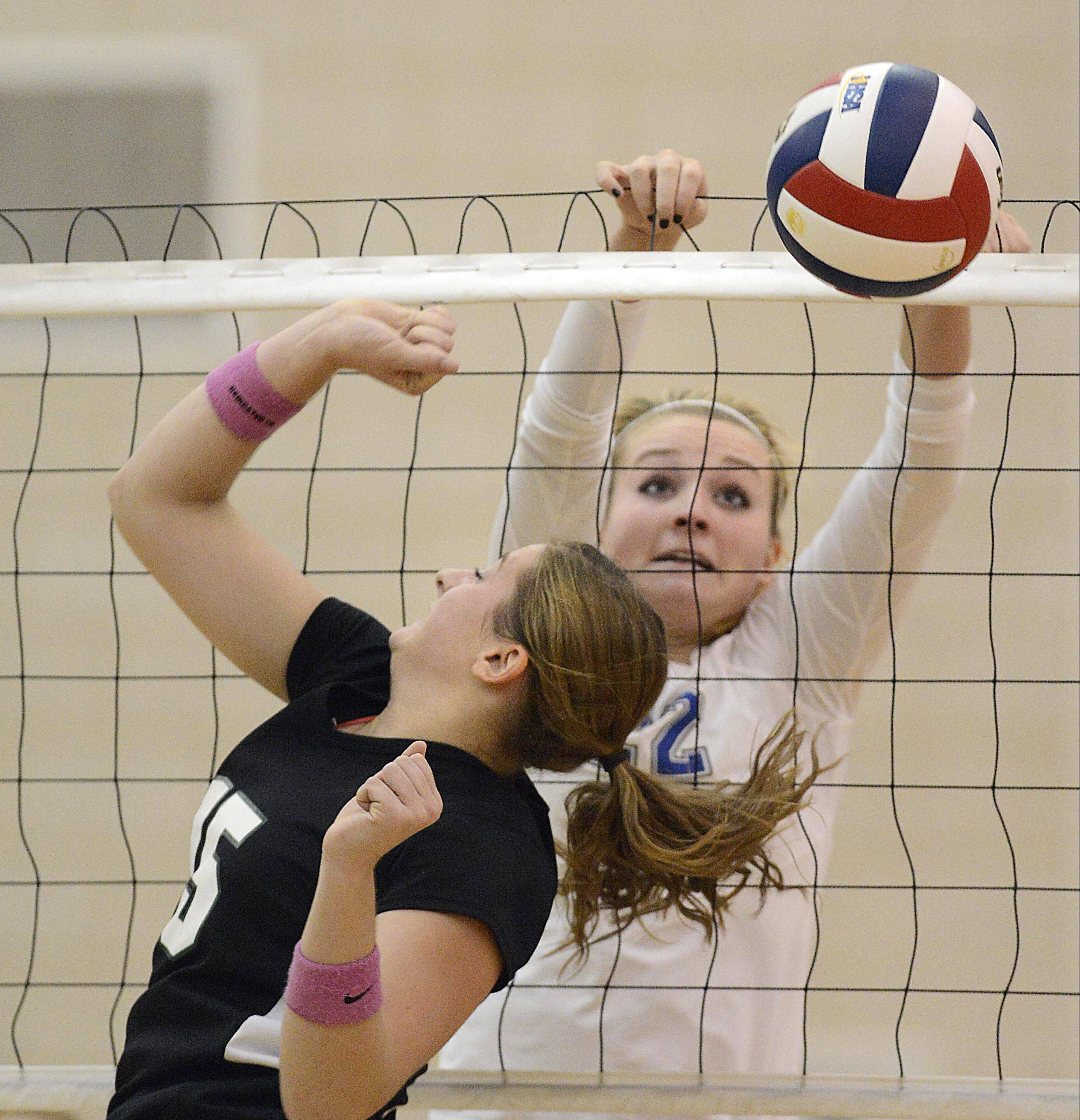 Geneva�s Maddie Courter gets the ball over the net against Glenbard West�s Abbey Winkler Tuesday in Geneva.