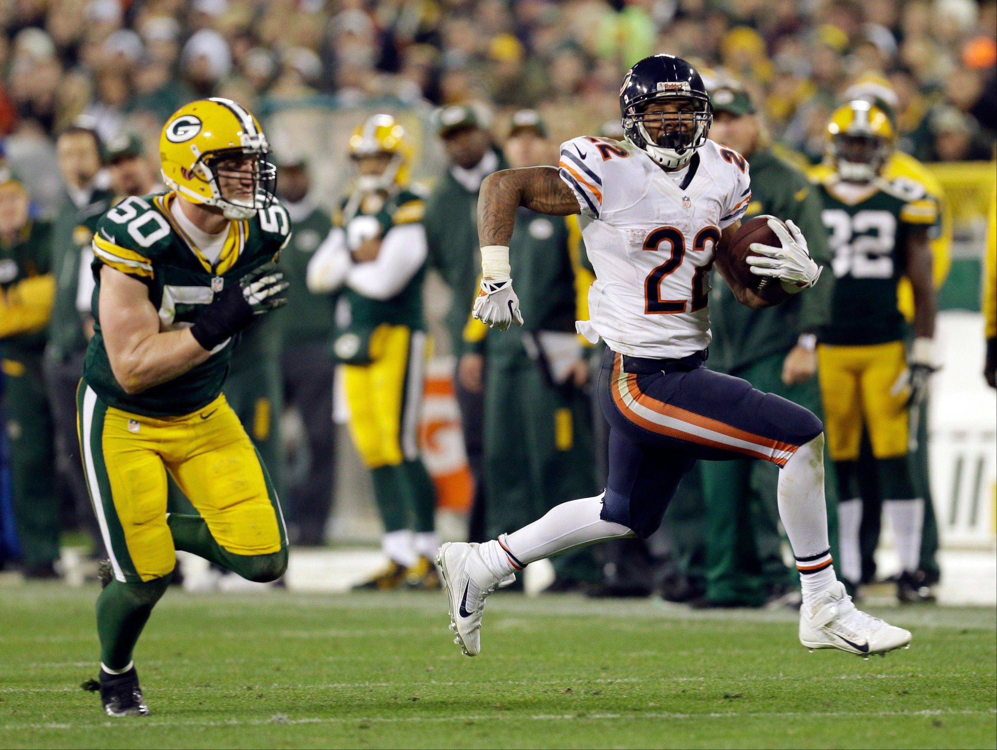 The Bears� Matt Forte sprints past the Packers� A.J. Hawk in the second half Monday. With 7:50 left in the game, Forte converted on fourth-and-inches from the Bears� 32 to prolong a game-saving drive.