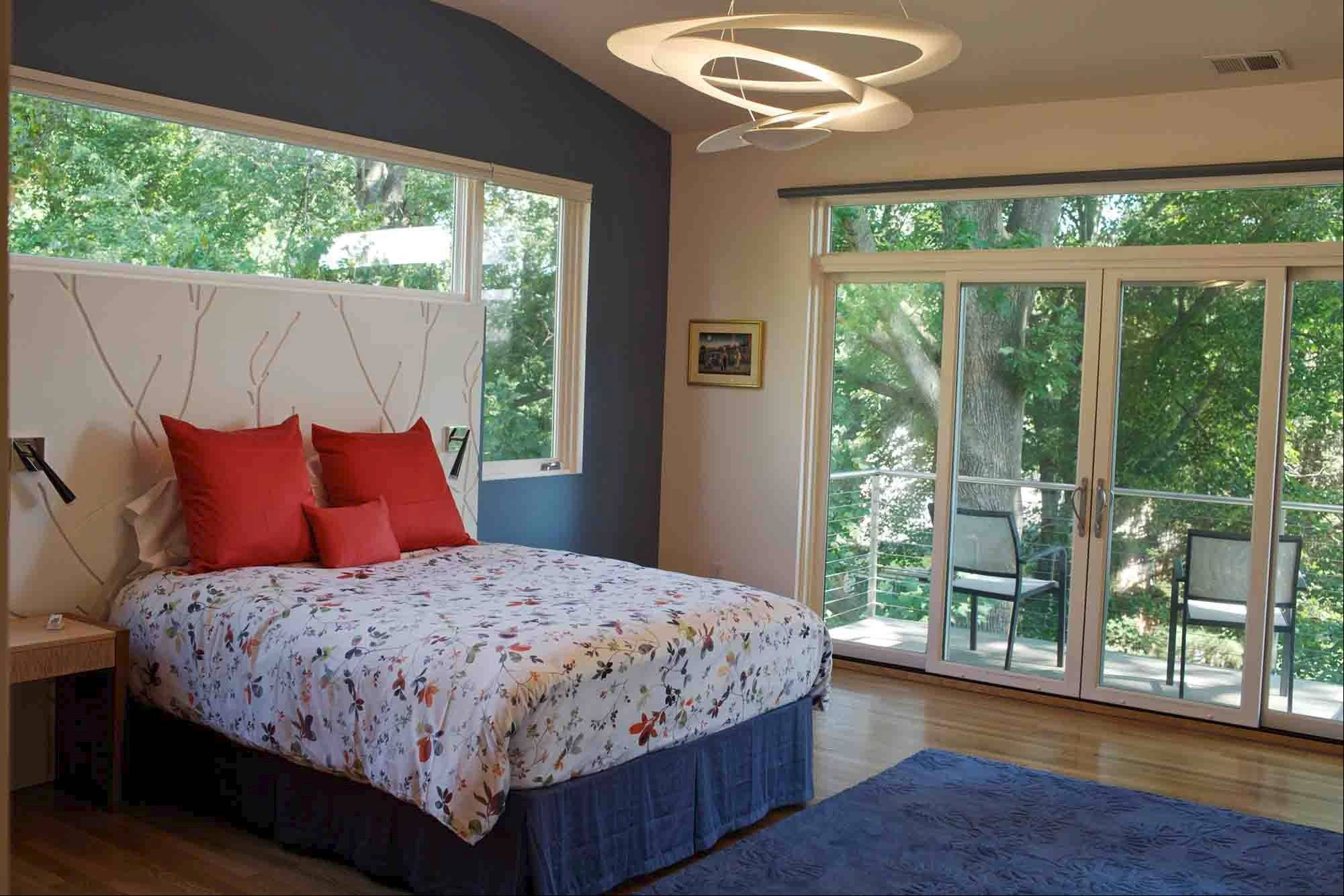 This view of the master bedroom shows the wall panels used in lieu of a headboard and the new balcony. The rug, purchased through ModernRugs.com, was made in a custom color by Nani Marquina and the Vibia slim wall lights were ordered through Yliving.com.