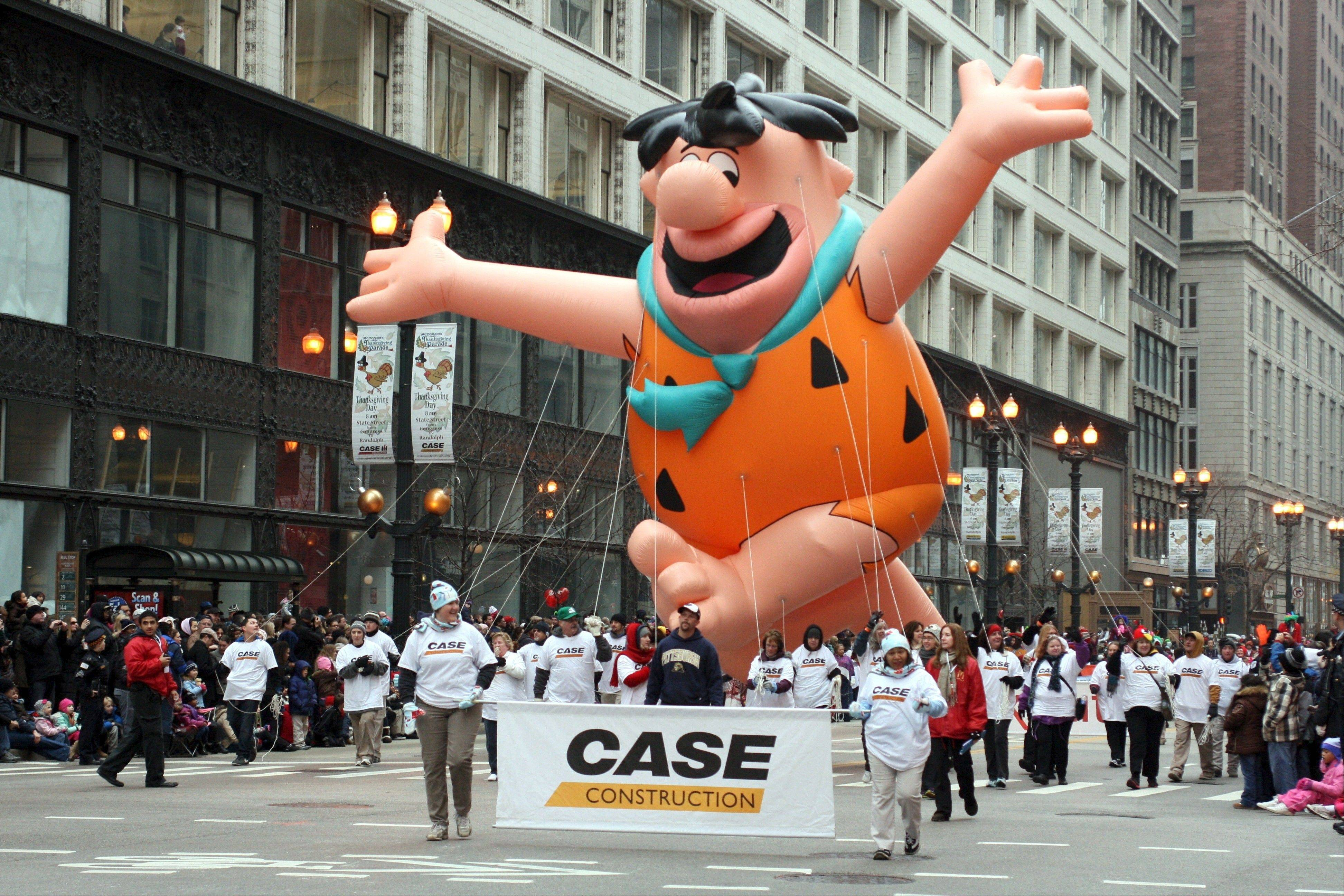 A contingent from Case Construction tends to an oversized balloon of Fred Flintstone in a previous edition of the McDonald's Thanksgiving Day Parade in Chicago.