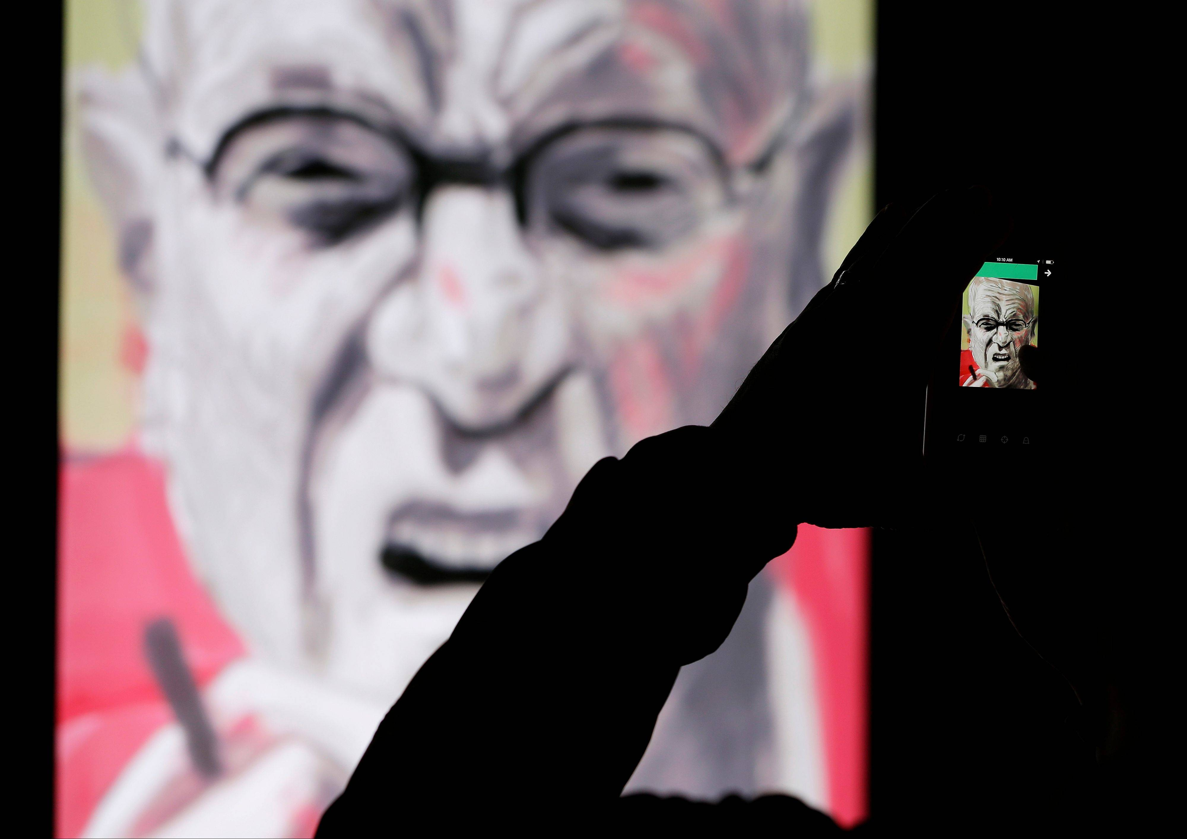 A man records how a painting made by David Hockney using an iPad takes shape at an exhibit at the de Young Museum in San Francisco.