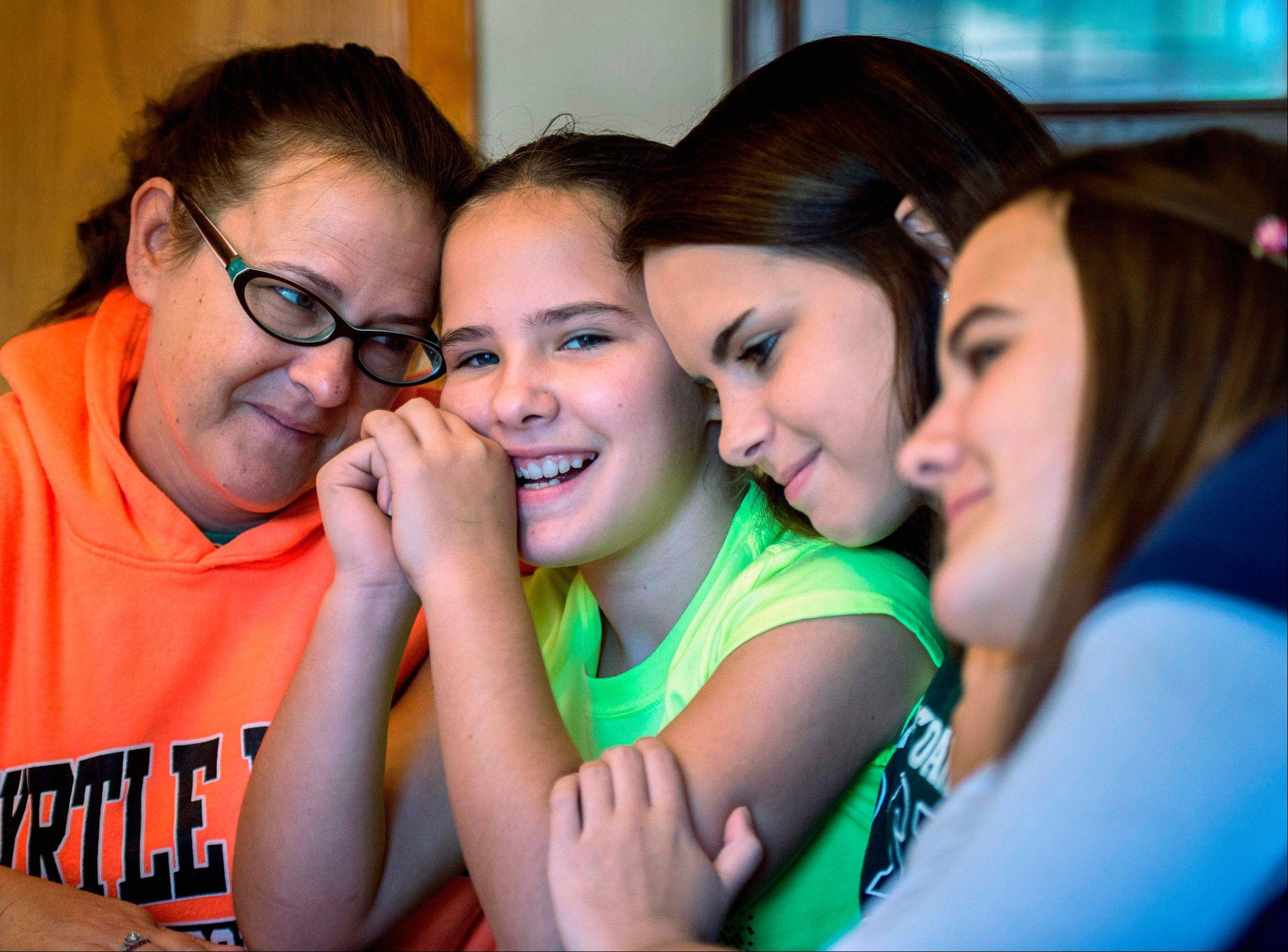 Molly Jackson, left, of Peoria, and three of her four daughters Priscilla, 11, center left, and Victoria, not pictured, suffer from what can only be described as a hyper-fever. The technical term for the disease is hyperimmunoglobulinemia D and periodic fever syndrome or HIDS. The two girls, along with sister, Brittaney, 14, far right, suffer juvenile idiopathic arthritis. Stephanie, 15, center right, has been untouched but is supportive of her sisters. The family is trying to raise funds for specialized treatment at John Hopkins.