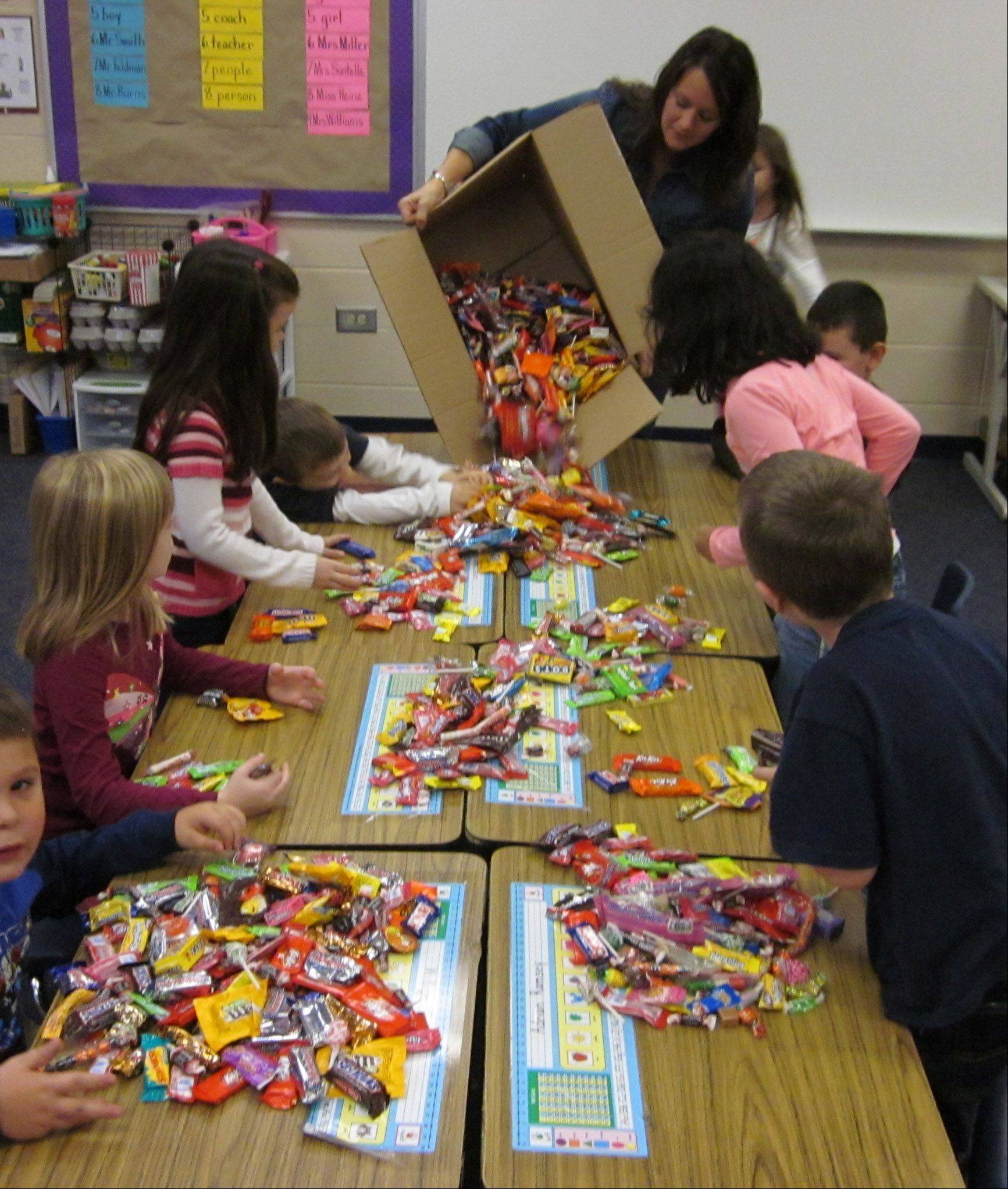 Jennifer Miller, first-grade teacher at Woodview School in Grayslake, has students in her classroom Tuesday sorting Halloween candy they donated for overseas U.S. troops.