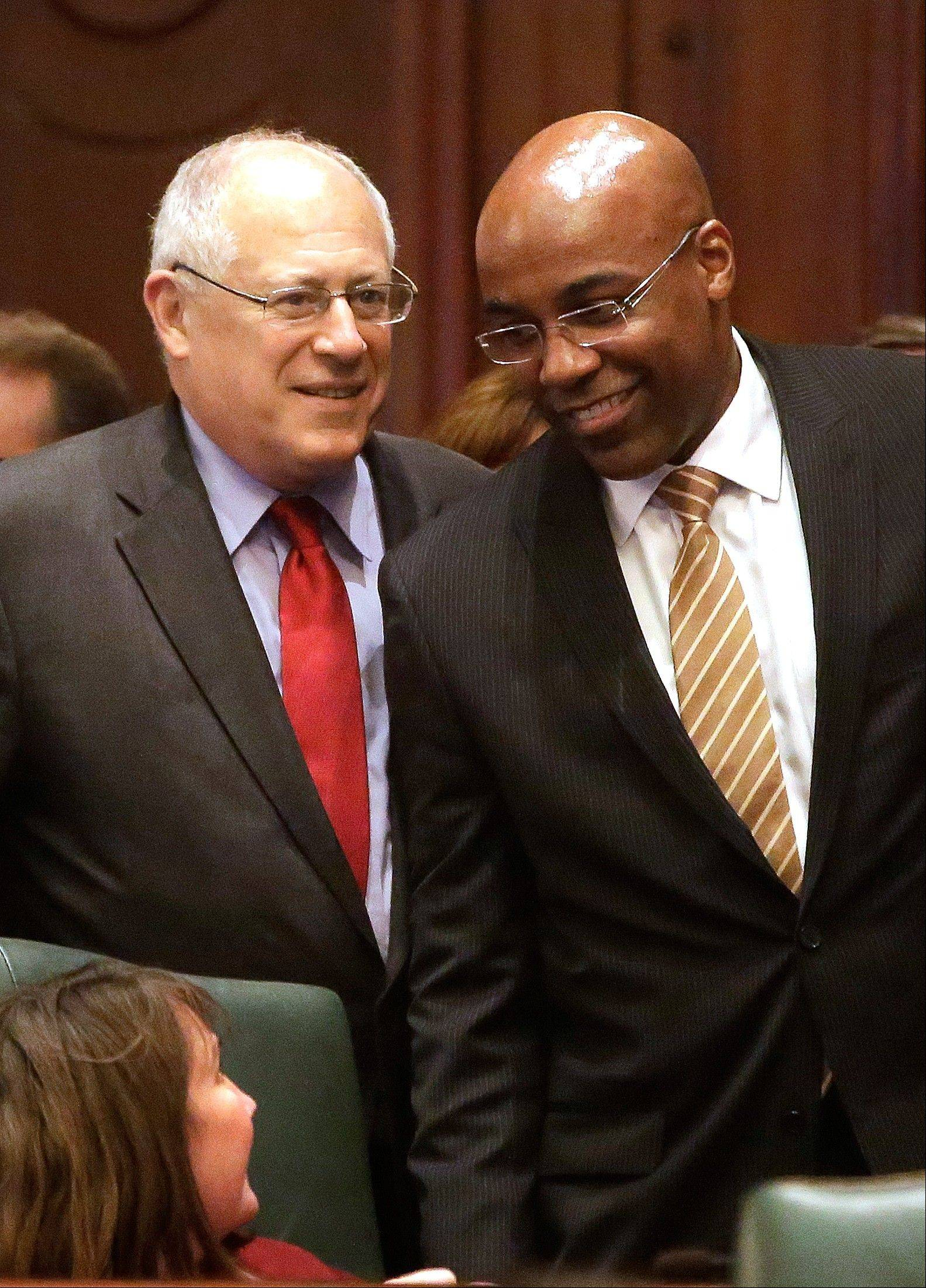Illinois Gov. Pat Quinn, left, and Illinois Sen. Kwame Raoul, D-Chicago, right, look on as gay marriage legislation passes on the House floor during veto session Tuesday, Nov. 5, 2013 in Springfield Ill.