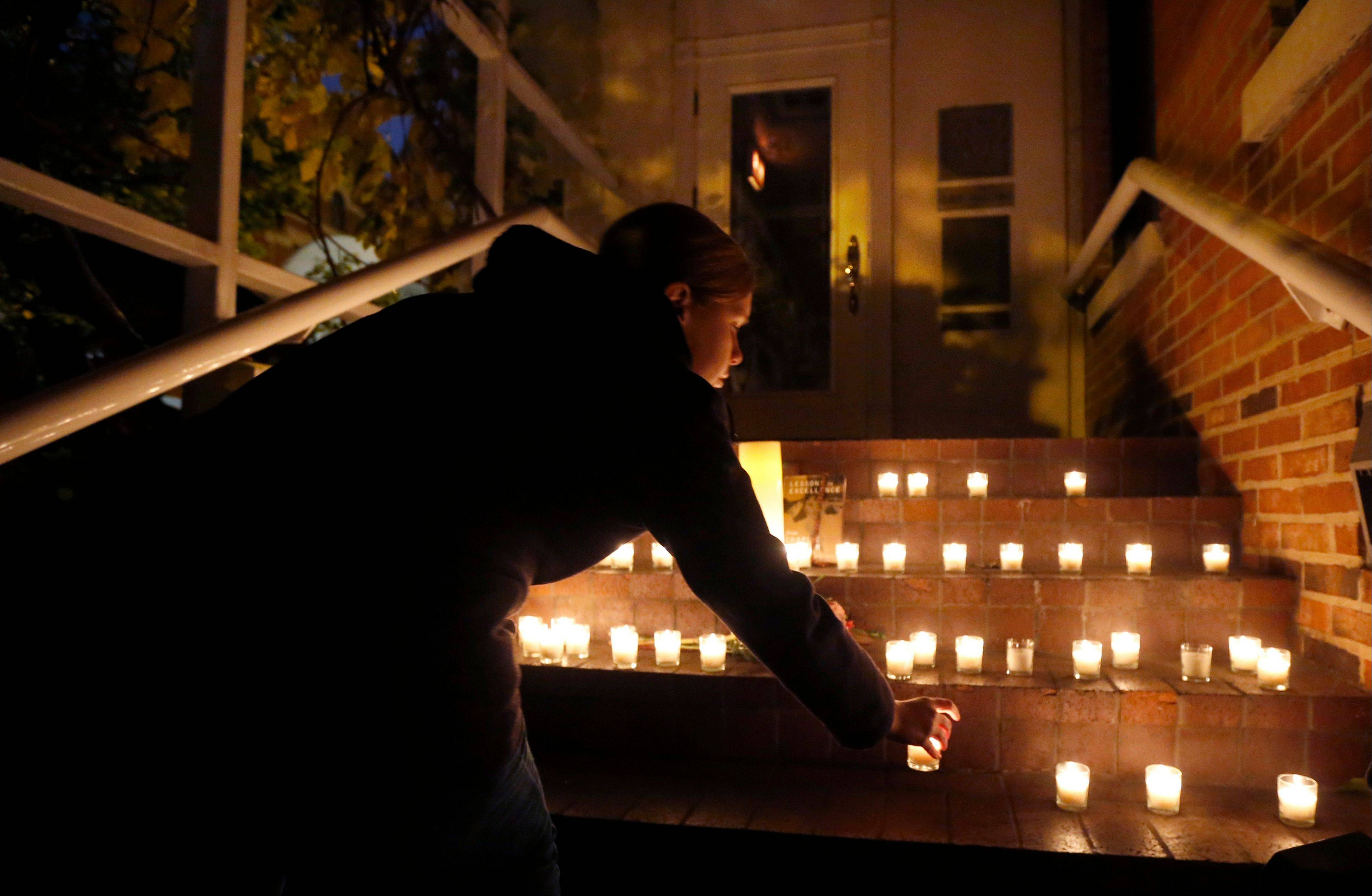 A woman places a candle on the steps of Chicago Chef Charlie Trotter's former restaurant after friends and former employees of Trotter's placed them there after a candle light tribute to Trotter, Tuesday, Nov. 5, 2013, in Chicago. Trotter, 54, died Tuesday, a year after closing his namesake Chicago restaurant that was credited with putting his city at the vanguard of the food world and training dozens of the nation's top chefs, including Grant Achatz and Graham Elliot.
