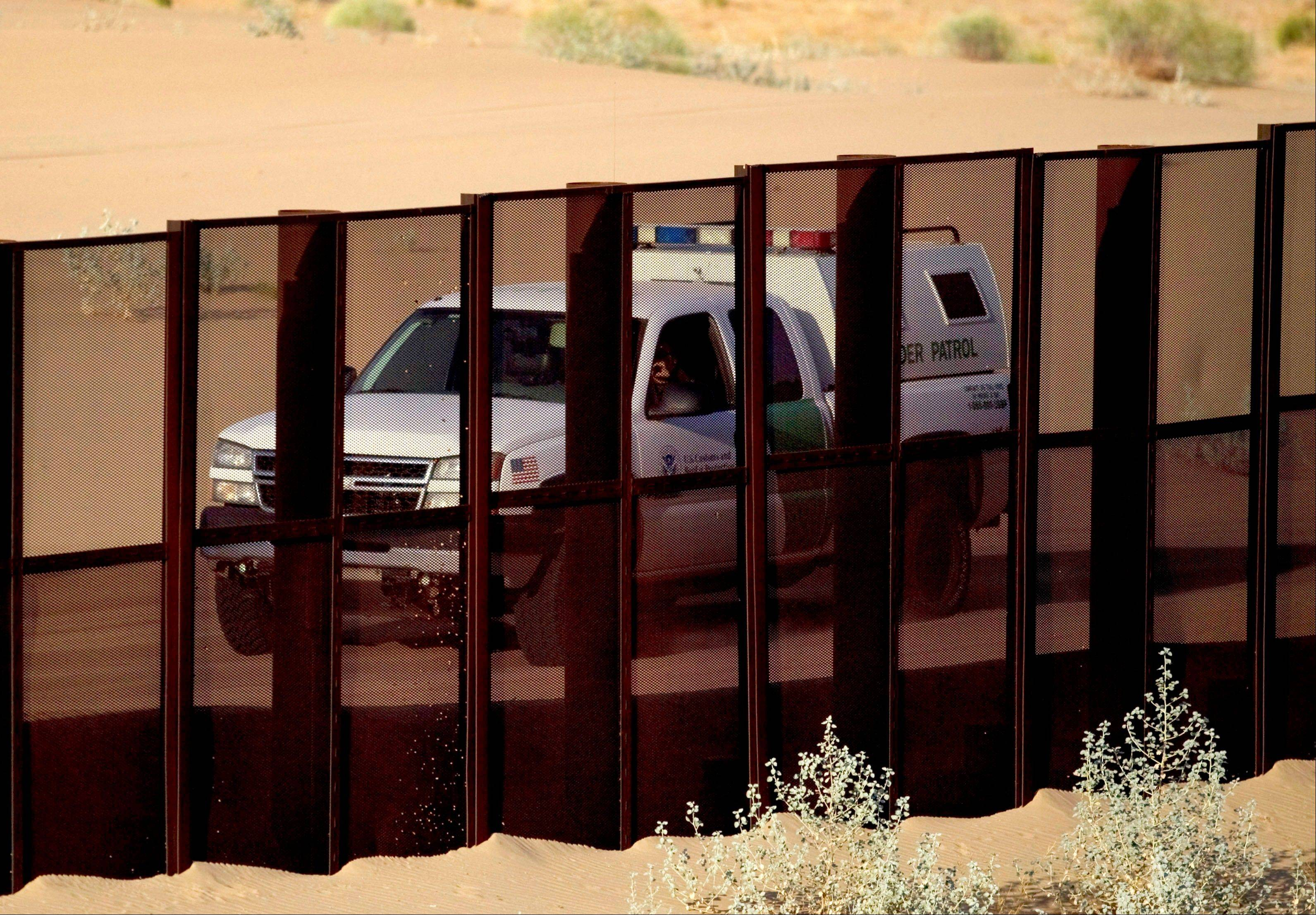 A U.S. border patrol vehicle drives along the U.S.-Mexico border fence near Yuma, Ariz., as seen from the outskirts of San Luis Rio Colorado, Mexico. The Border Patrol's parent agency decided to continue allowing agents to use deadly force against rock-throwers and assailants in vehicles, despite recommendations of a government commissioned review to end the practice.