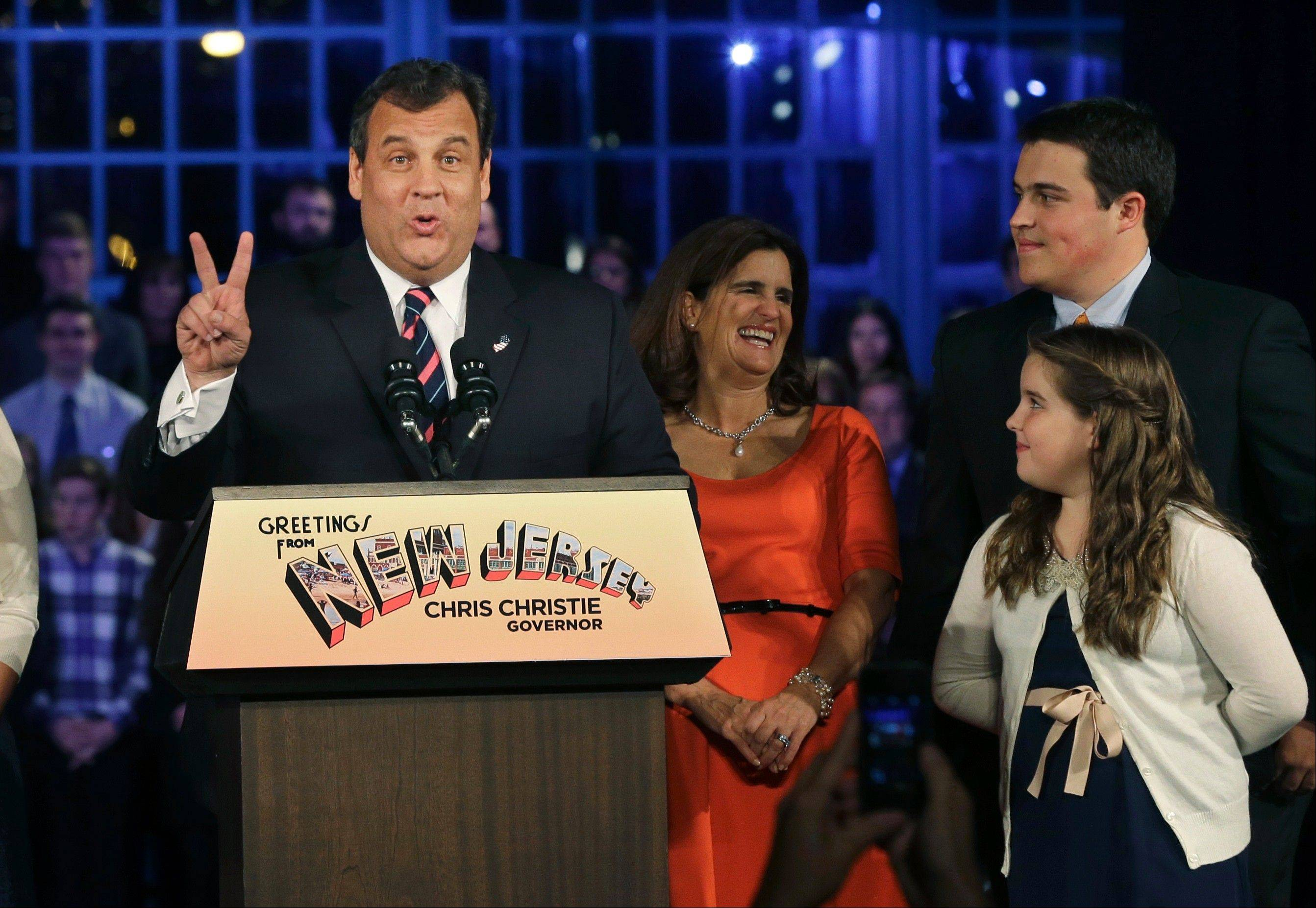 Republican New Jersey Gov. Chris Christie signals a second term as he stands with his wife, Mary Pat Christie, second right, and children, Andrew, back right, Bridget, right, while celebrating his re-election Tuesday.