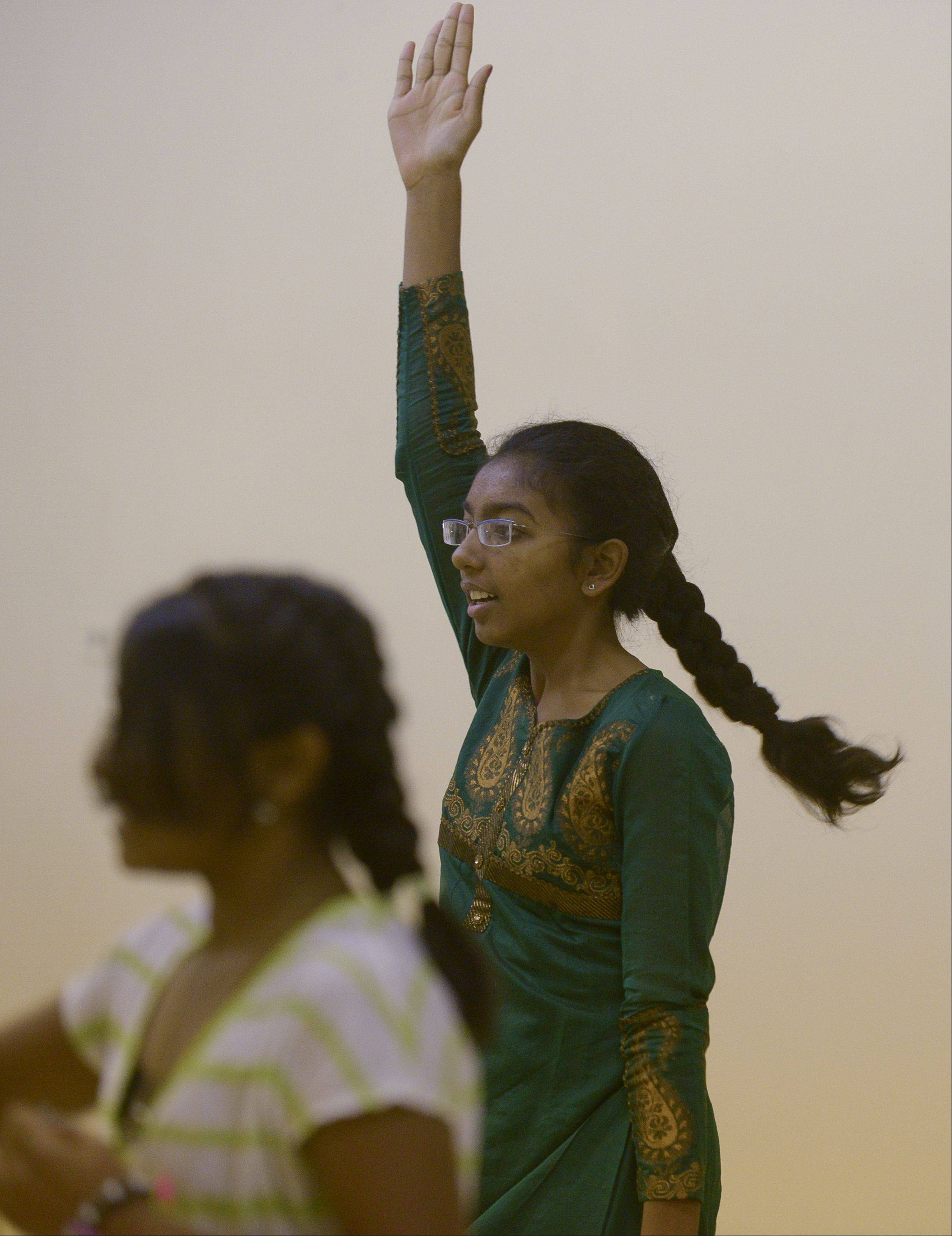 Rhea Singh, 14, of Lisle, practices to dance Sunday morning along the route of the Inaugural Edward Hospital Naperville Marathon and Half Marathon with fellow students at Bollywood Rhythms studio in Naperville.