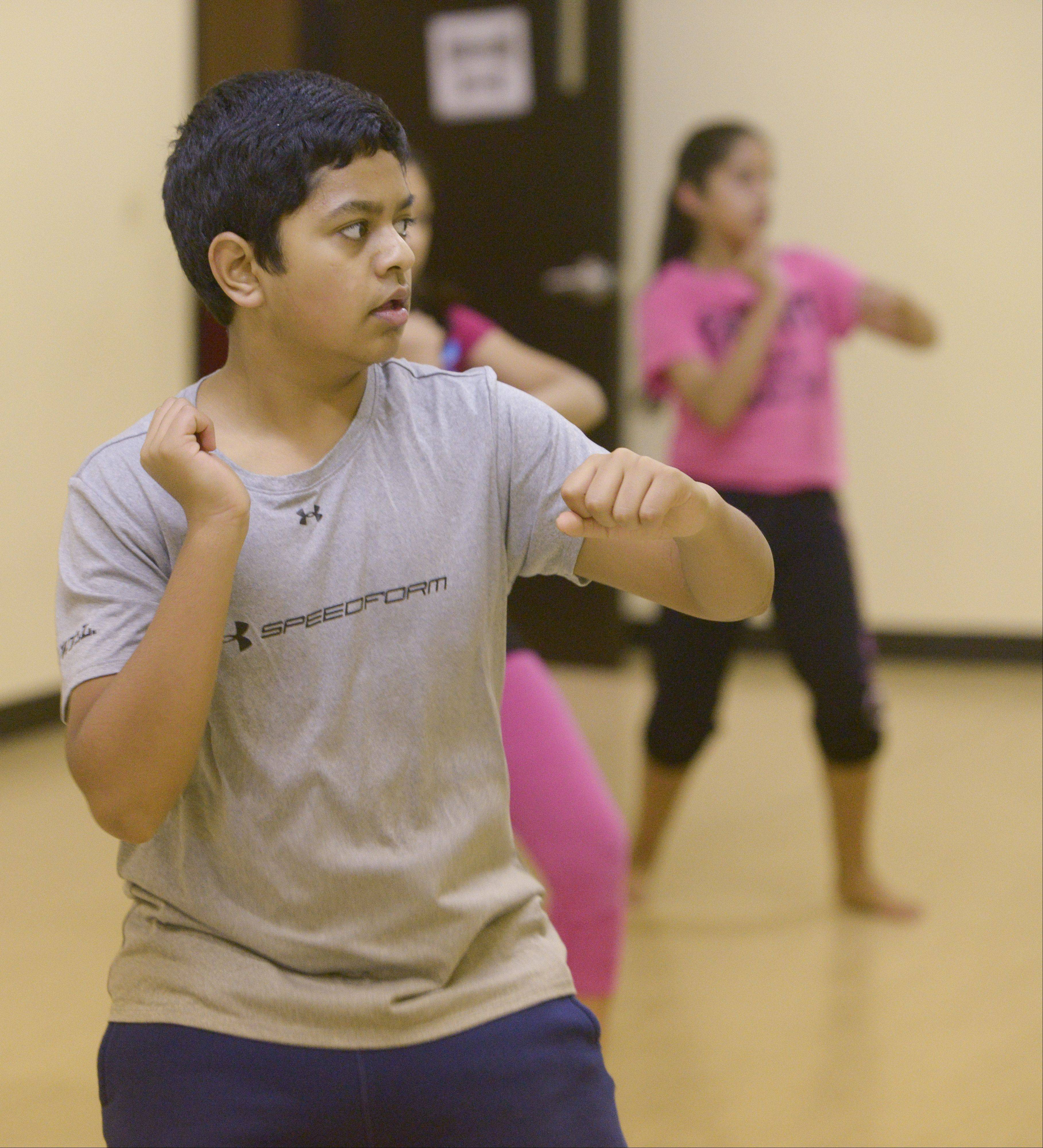 Bollywood Rhythms dance studio student Dhruv Nagesh, 12, of Naperville, practices with his classmates who will be performing Sunday morning along the route of the Inaugural Edward Hospital Naperville Marathon and Half Marathon.