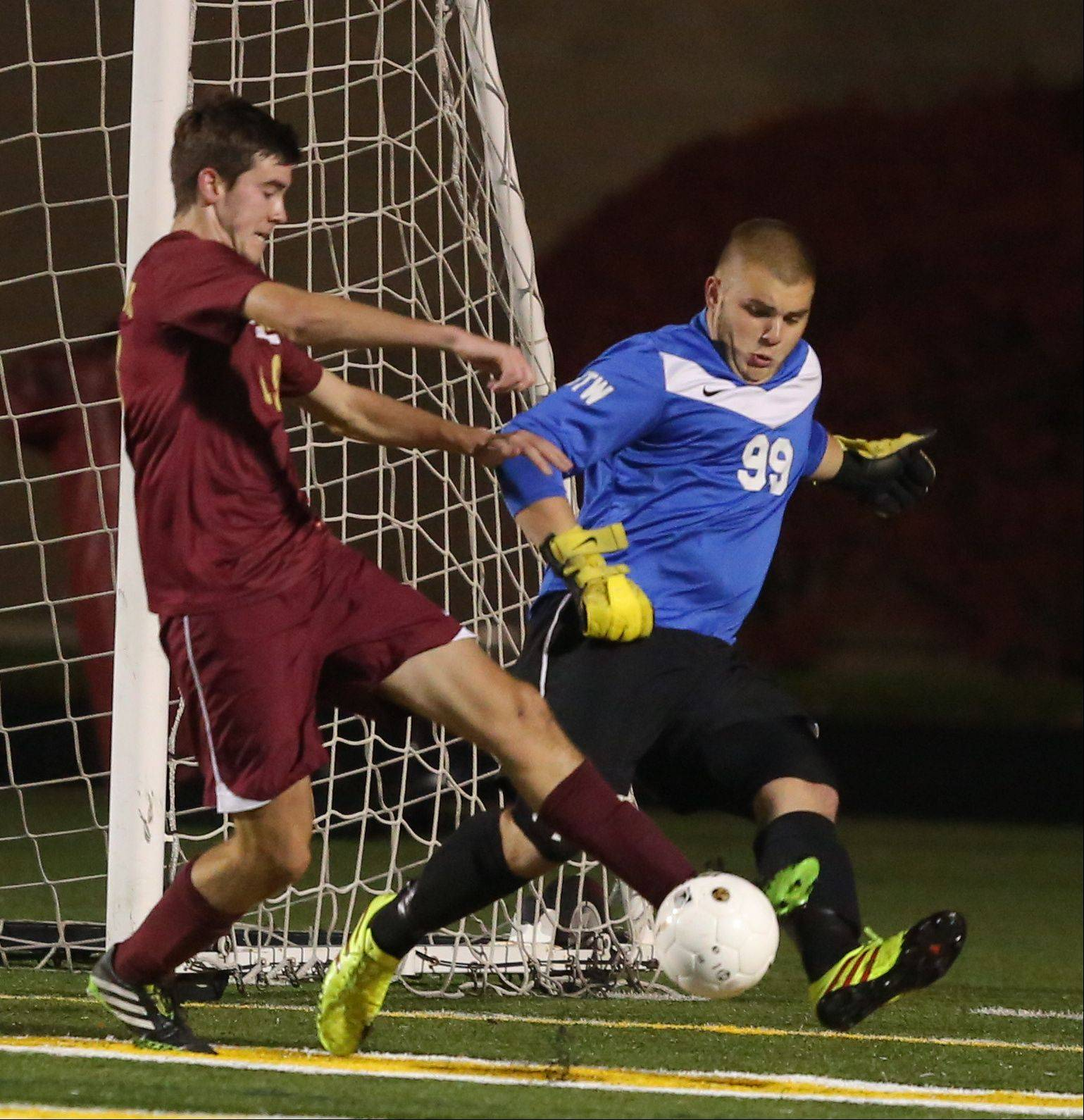 Antioch goalie Tommy Tritschler, right, battles with St. Ignatius' John Devitt during the Class 2A supersectional Tuesday night at Stevenson.