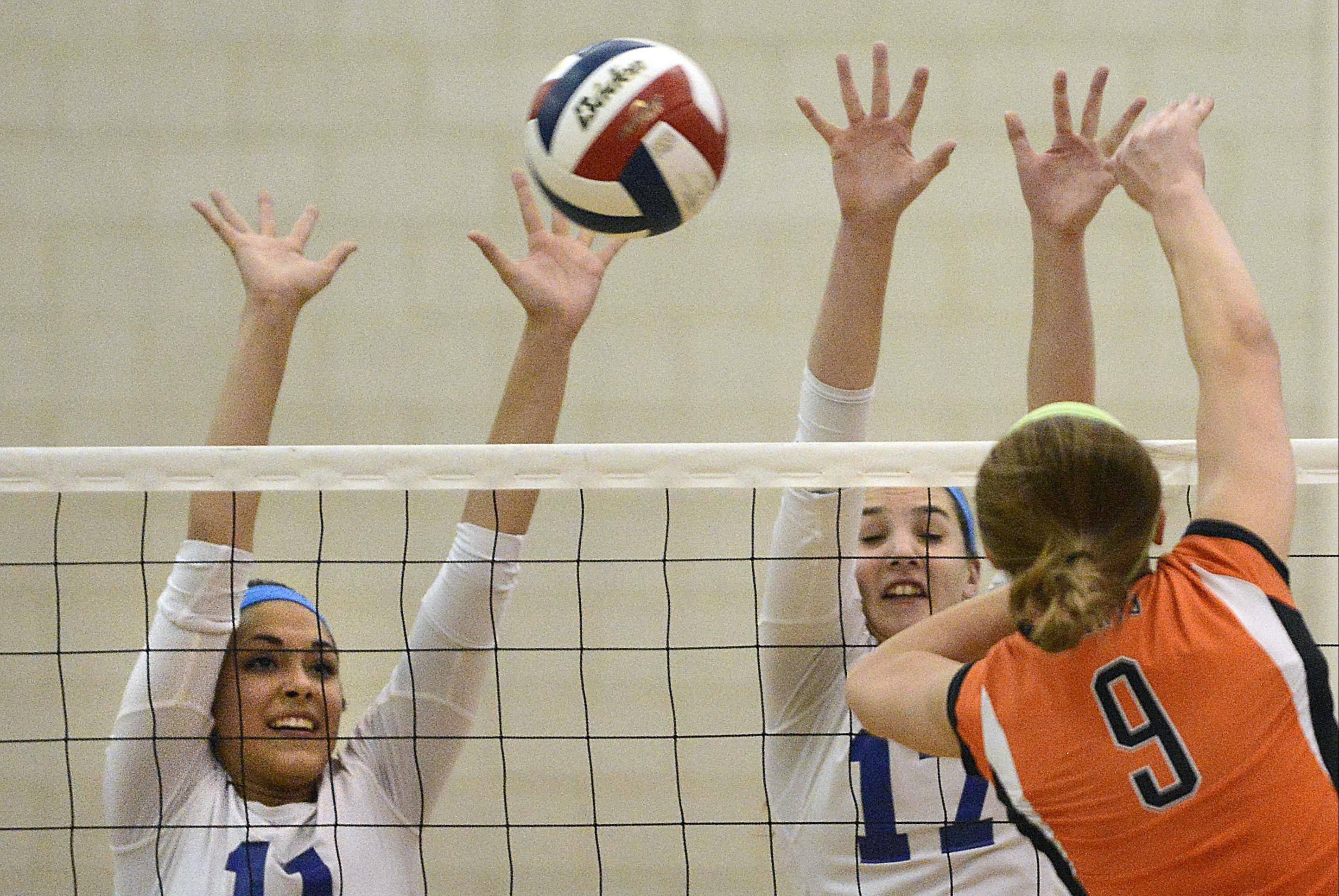 St. Charles North's Sophia DuVall, left, and Daley Krage block a shot by St. Charles East's Megan Schildmeyer Tuesday in Geneva.