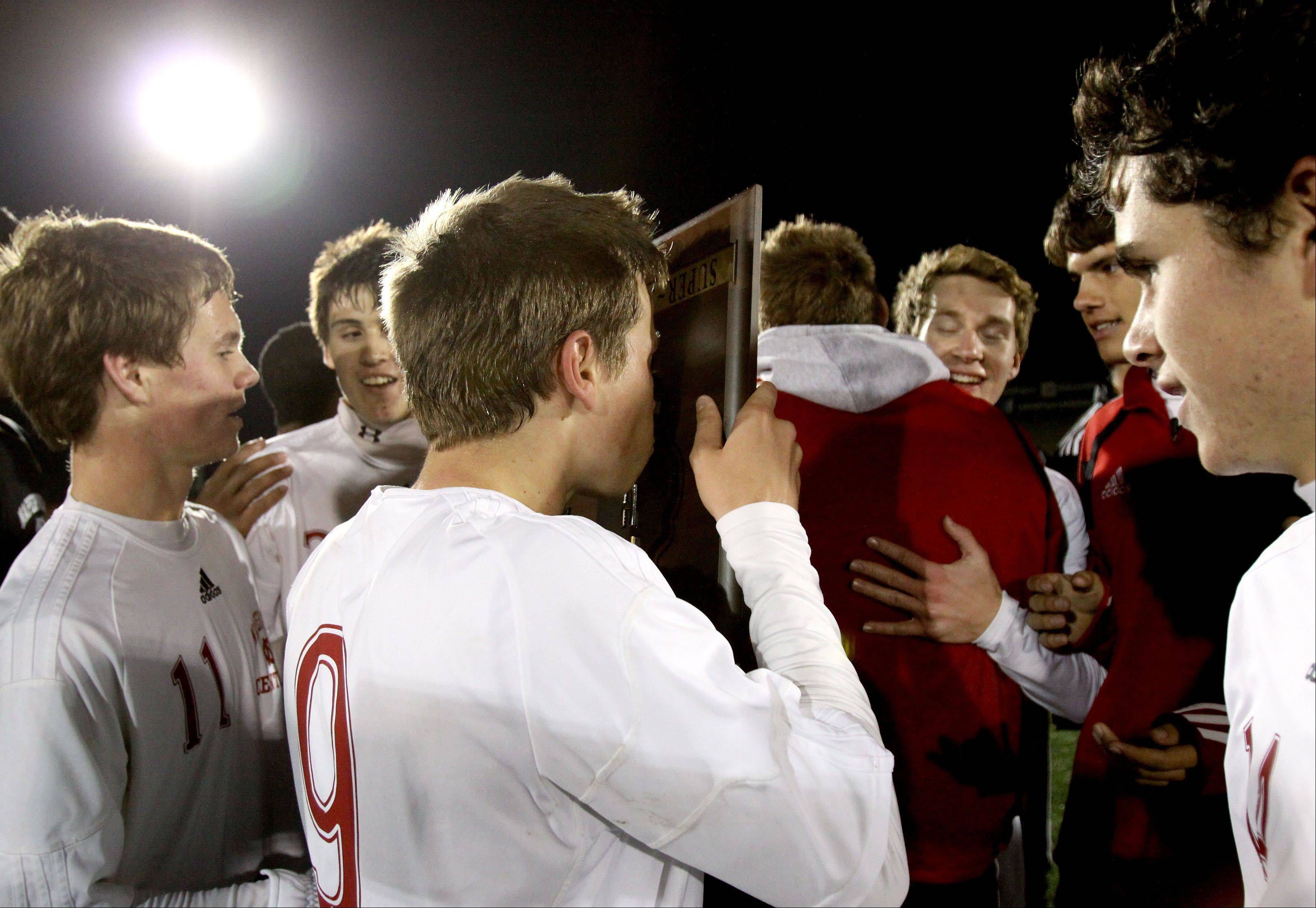 Naperville Central teammates take turn kissing the plaque after they beat Morton 2-0 in Class 3A super-sectional soccer in Romeoville on Tuesday.