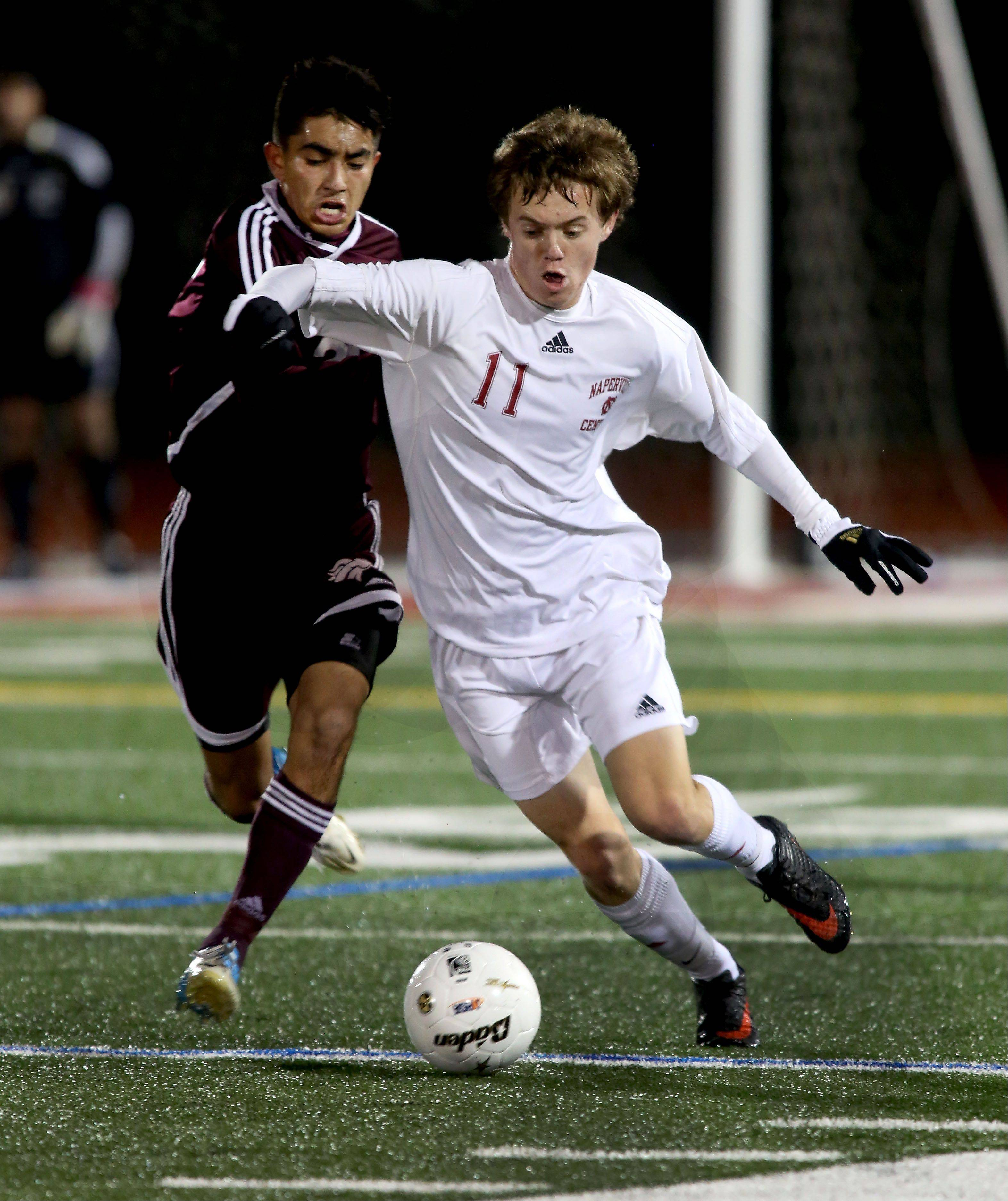 Ben Border of Naperville Central, right, takes the ball from Leo Delgado of Morton, left, during Class 3A super-sectional soccer in Romeoville on Tuesday.