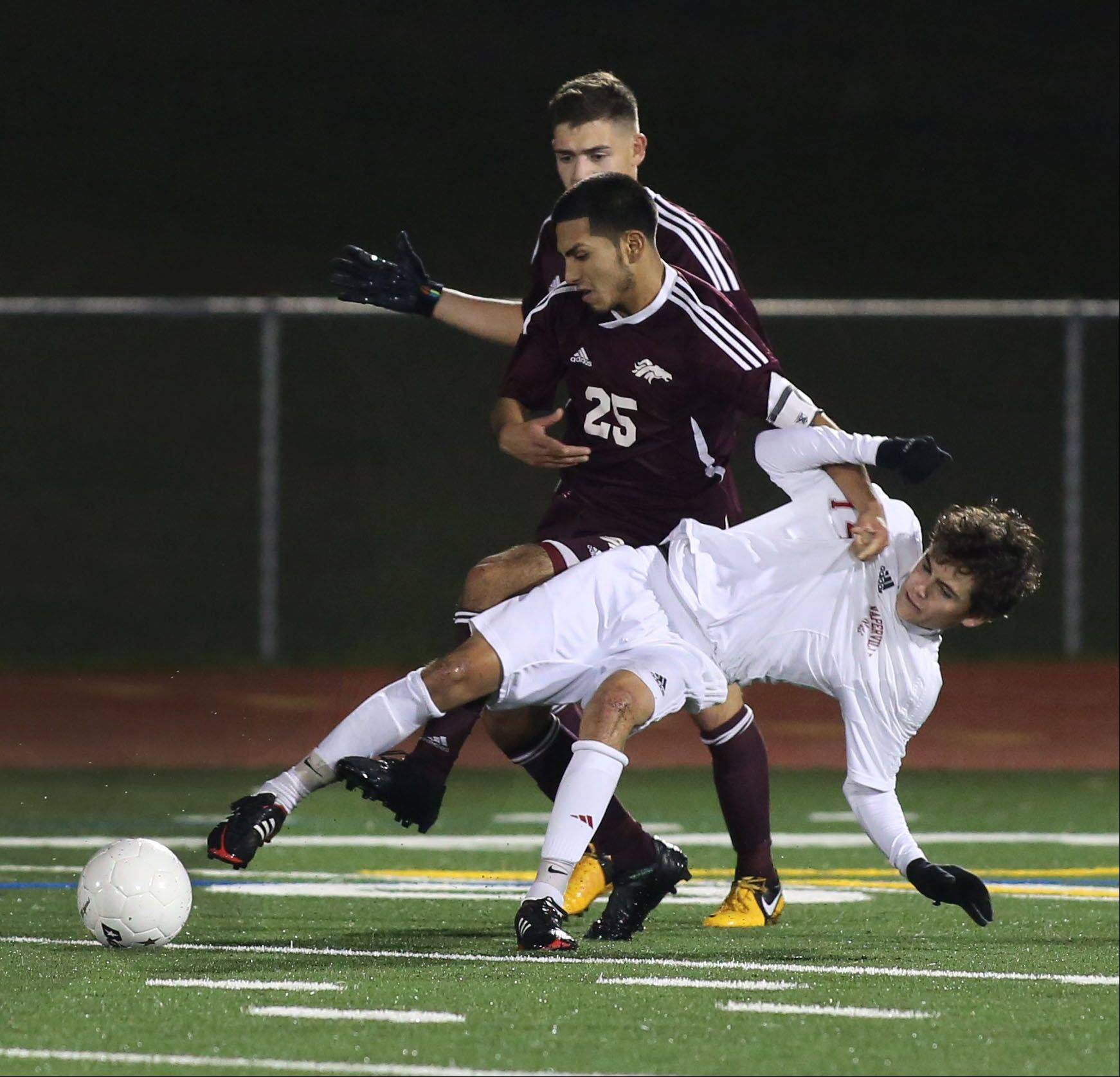 David Murphy of Naperville Central gets tripped up by Edgar Garcia, left, of Morton during Class 3A super-sectional soccer in Romeoville on Tuesday.