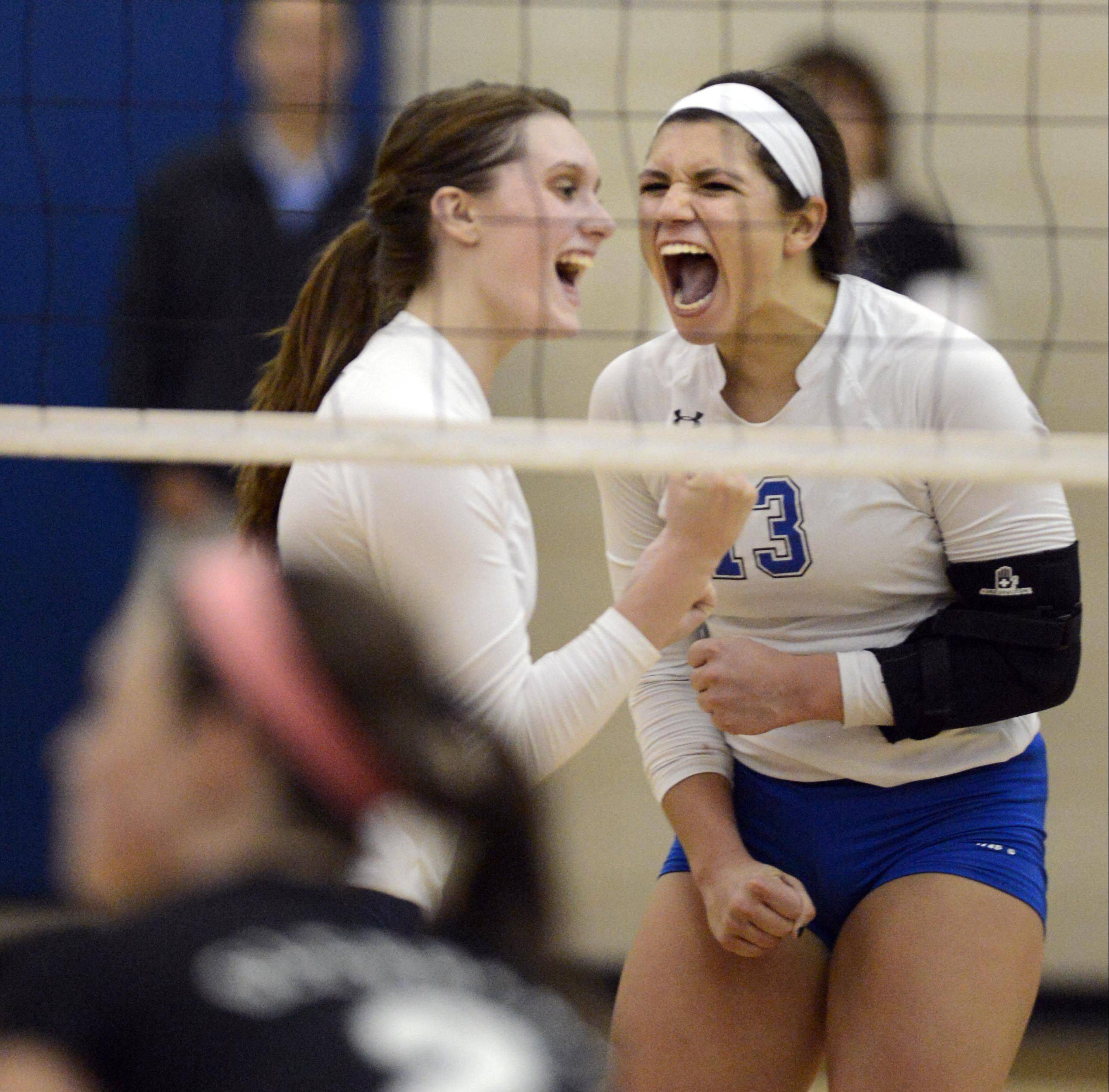 Geneva's Hannah Lanasa, left, and Courtney Caruso celebrate a point late in the Vikings' win over Glenbard West Tuesday in Geneva.