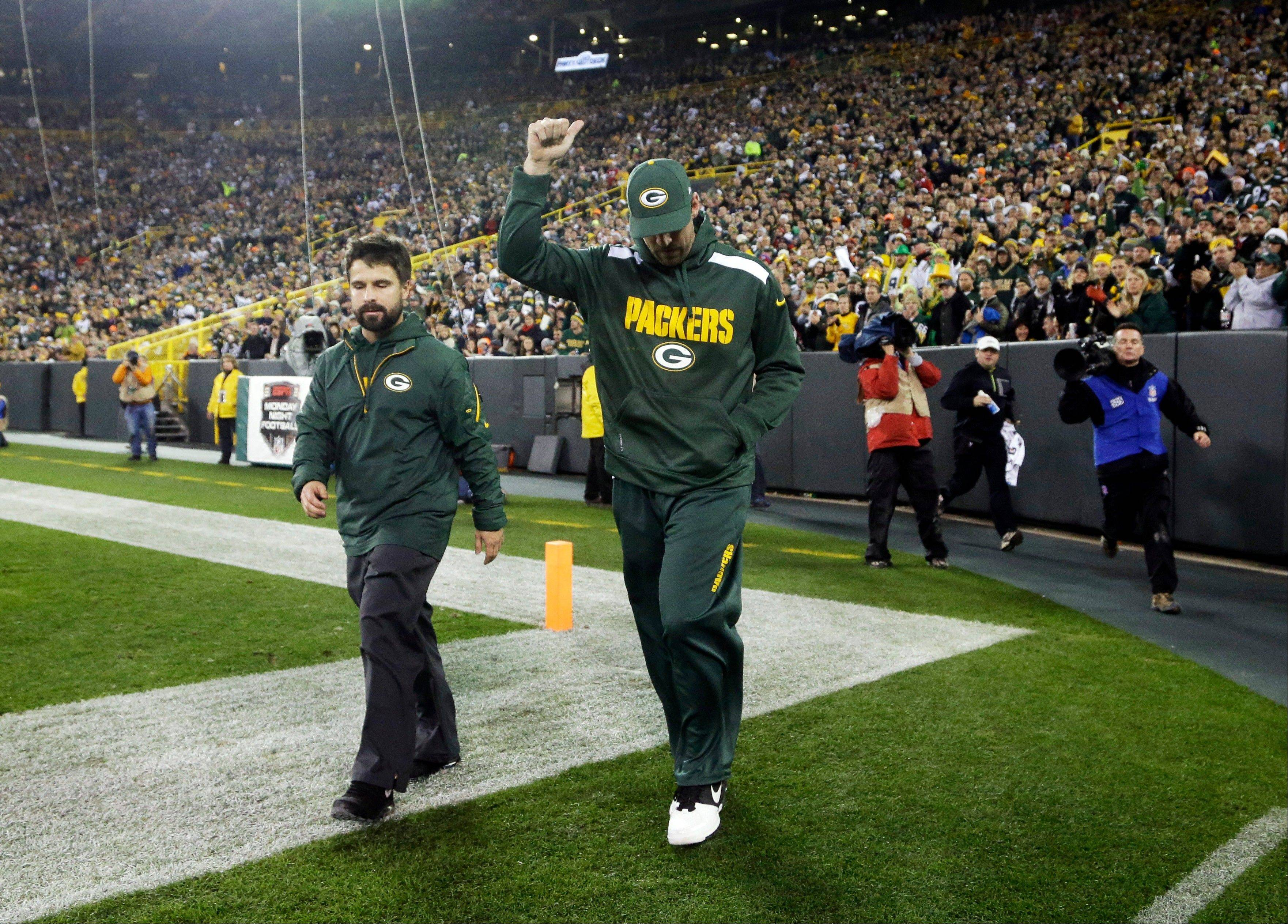 Green Bay Packers' Aaron Rodgers gives a thumbs up to fans as he walks back onto the field during the second half. Rodgers left the game in the first half after being sacked by Shea McClellin.