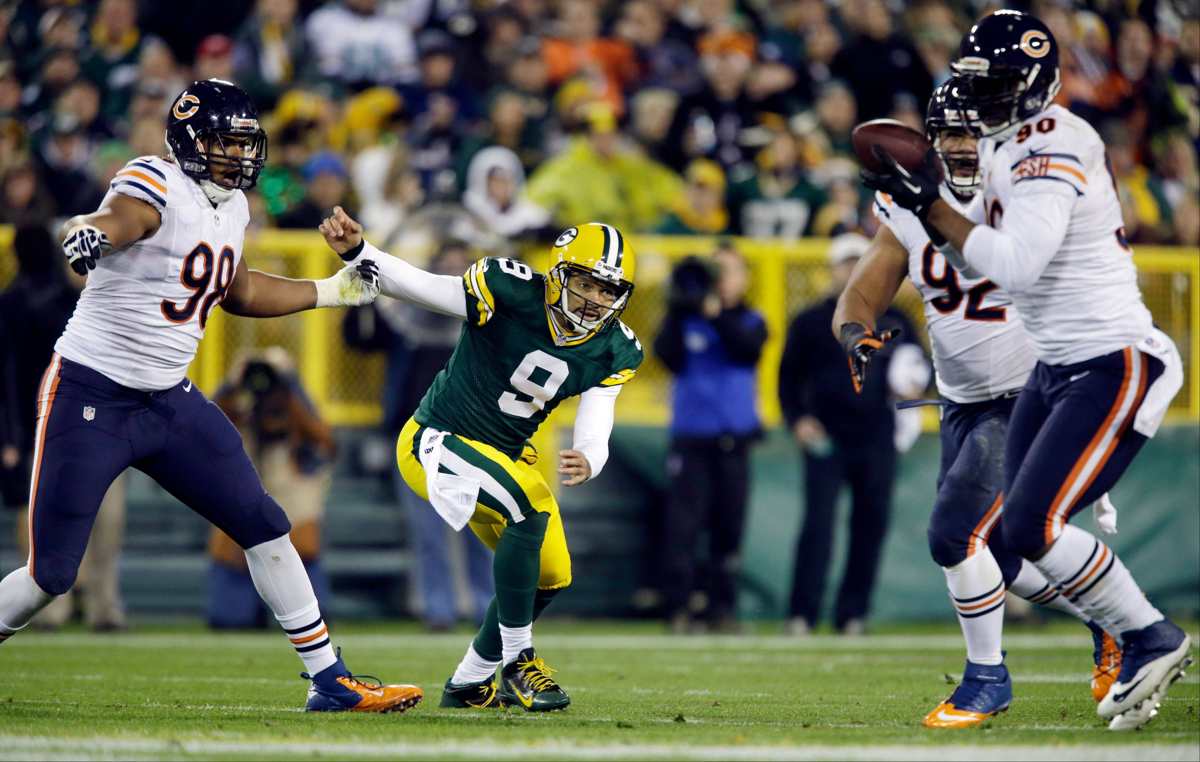 Green Bay Packers quarterback Seneca Wallace watches as Chicago Bears' Julius Peppers (90) intercepts a pass during the first half .