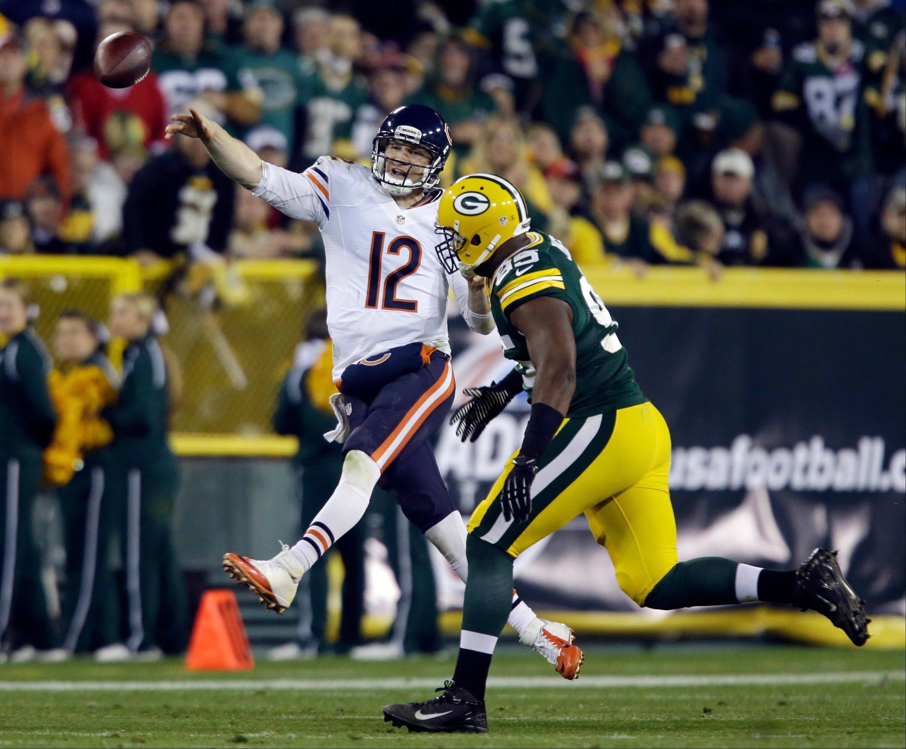 Chicago Bears quarterback Josh McCown throws past Green Bay Packers' Datone Jones during the second half .