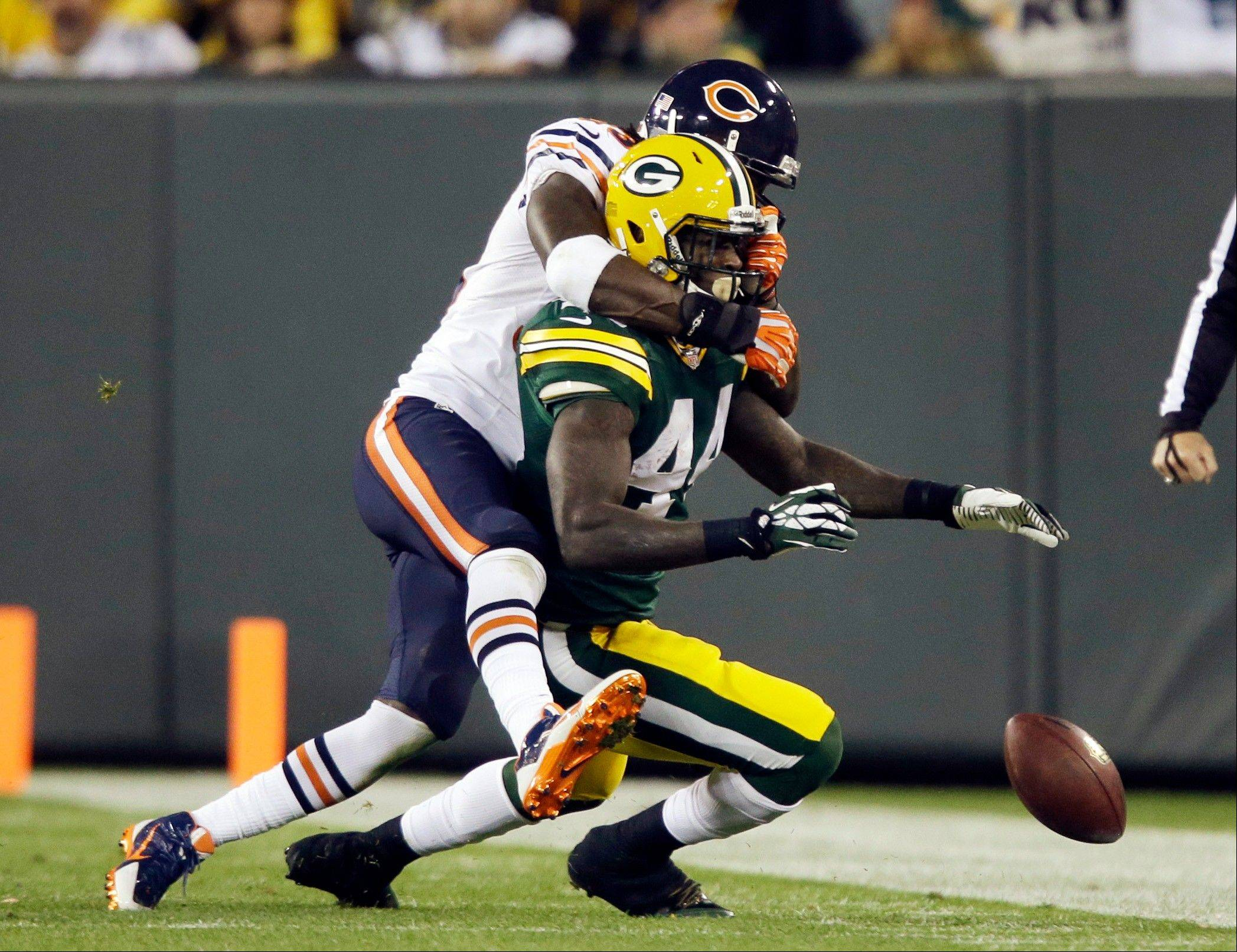 Green Bay Packers' James Starks fumbles out of bounds as he is hit by Chicago Bears' Charles Tillman during the first half .