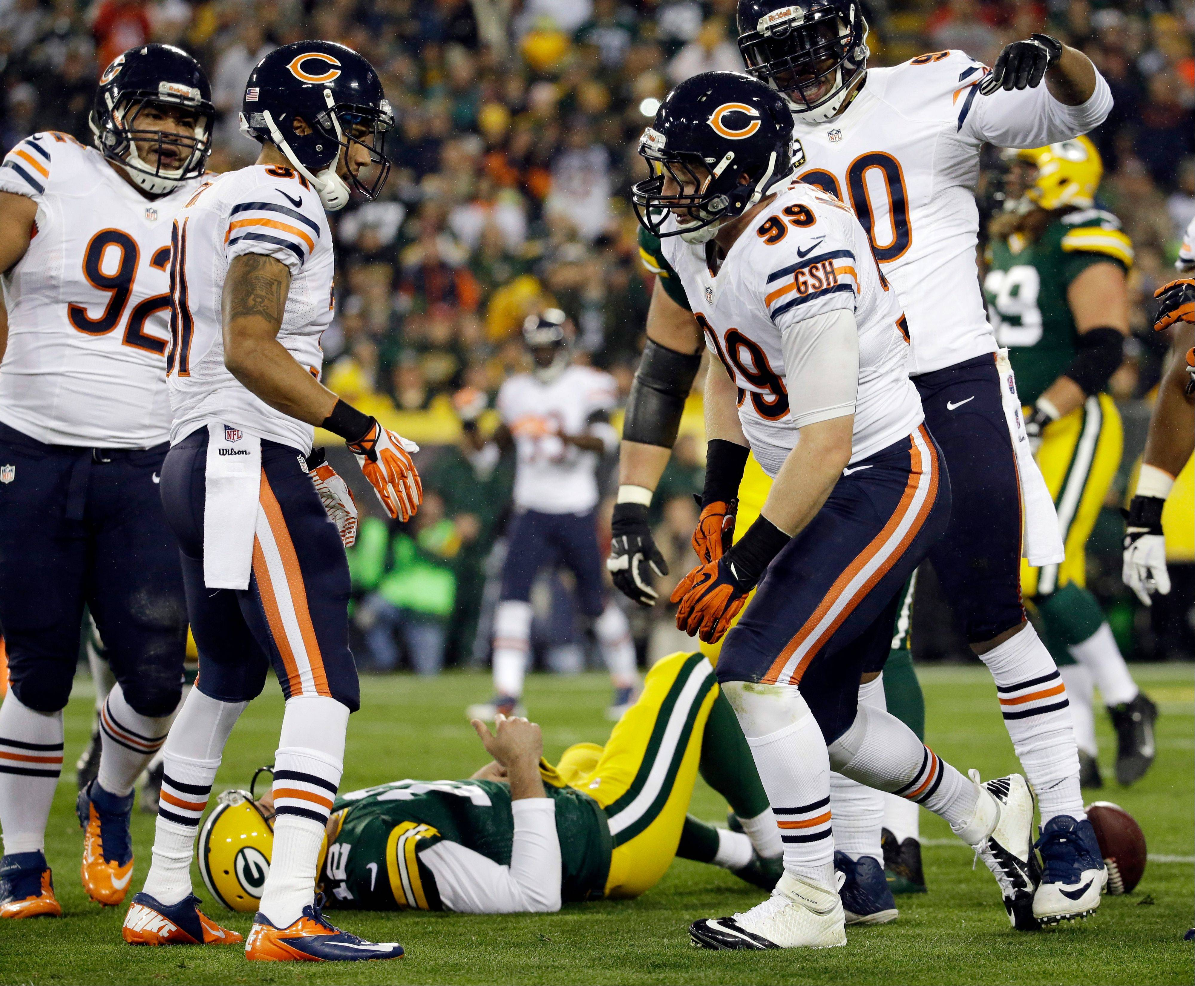 Green Bay Packers' Aaron Rodgers lays on the ground after being sacked by Chicago Bears' Shea McClellin during the first half .