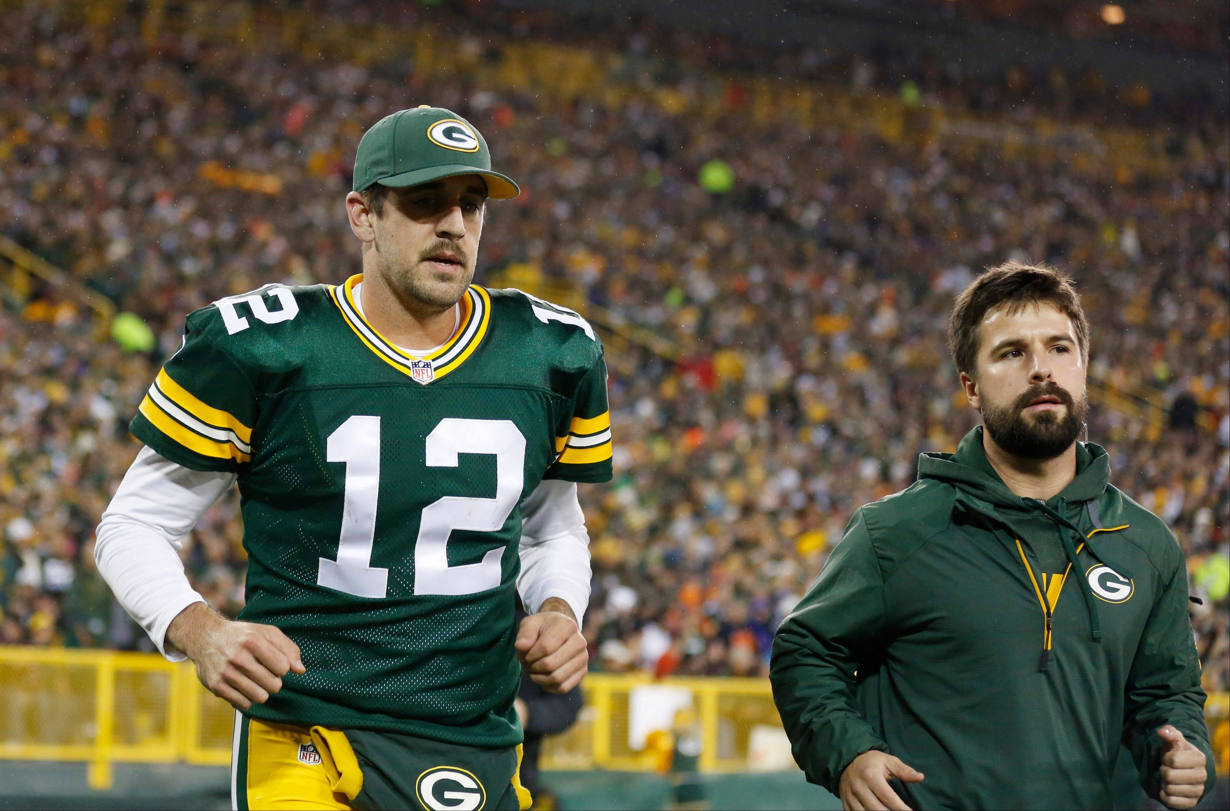 Green Bay Packers' Aaron Rodgers heads to the locker room after being hurt during the first half .