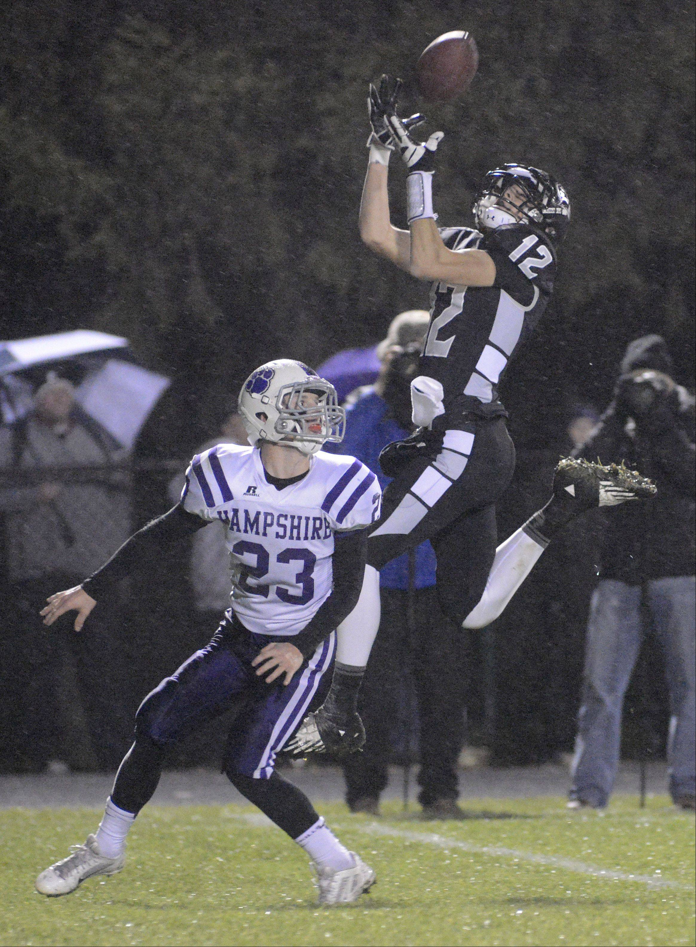 Kaneland's John Pruett leaps to complete a pass over Hampshire's Trey Schramm during Friday's football game.