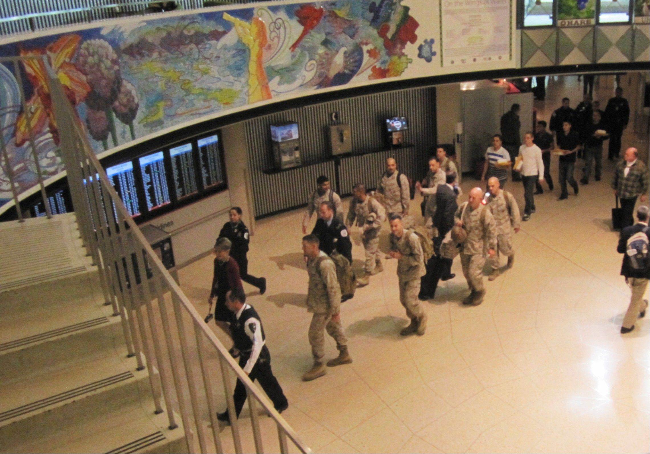 Marines walk through a terminal at O�Hare International Airport during part of their journey back home after a tour of duty in Afghanistan. The Marines were treated like heroes at the airport after a retired Marine and some others were not going to let them make the final leg of their journey to San Diego without thanking them for their service.