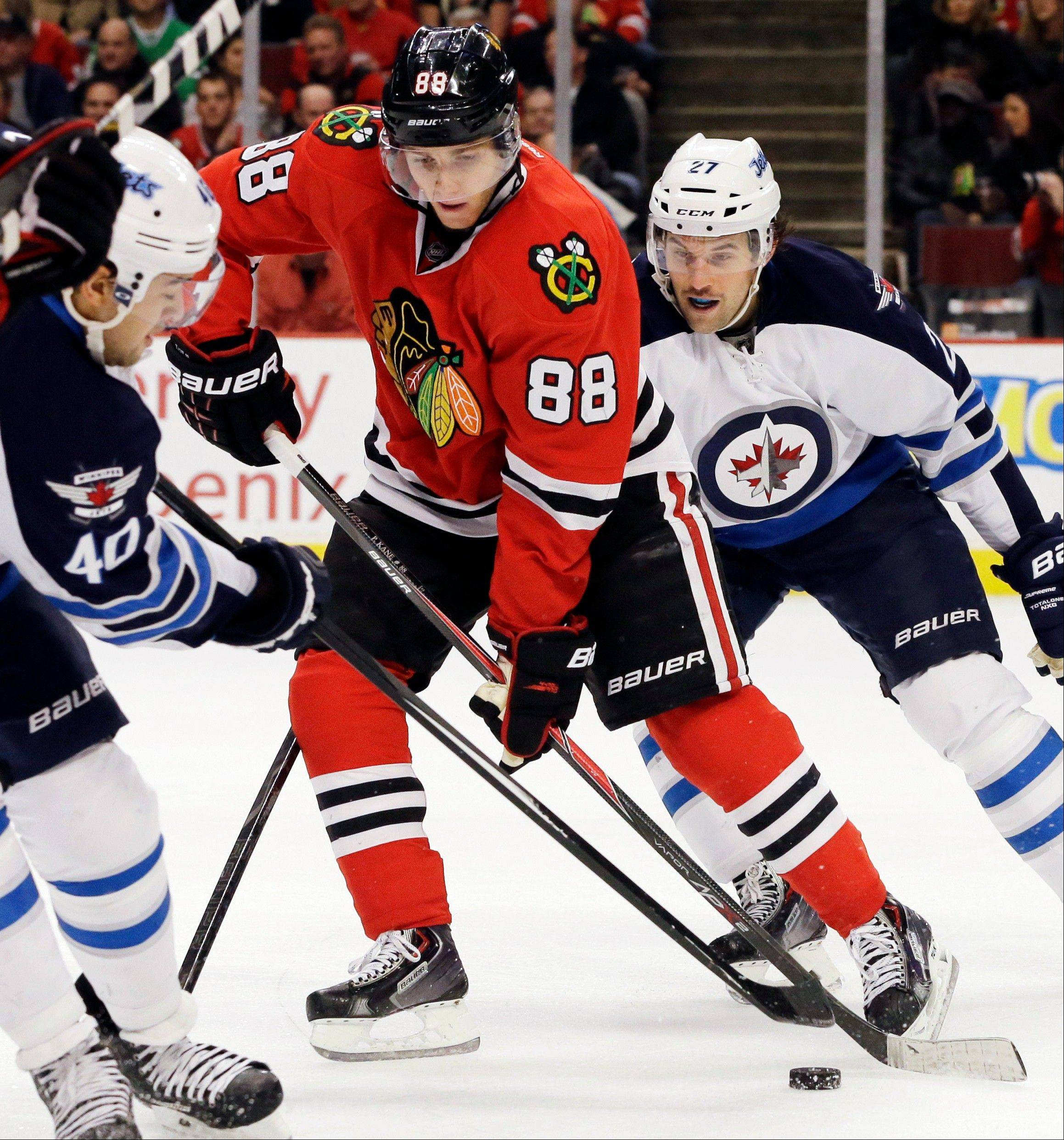 Chicago Blackhawks' Patrick Kane (88) controls the puck against Winnipeg Jets' Devin Setoguchi, left, and Eric Tangradi during the second period of an NHL hockey game in Chicago, Wednesday, Nov. 6, 2013. (AP Photo/Nam Y. Huh)