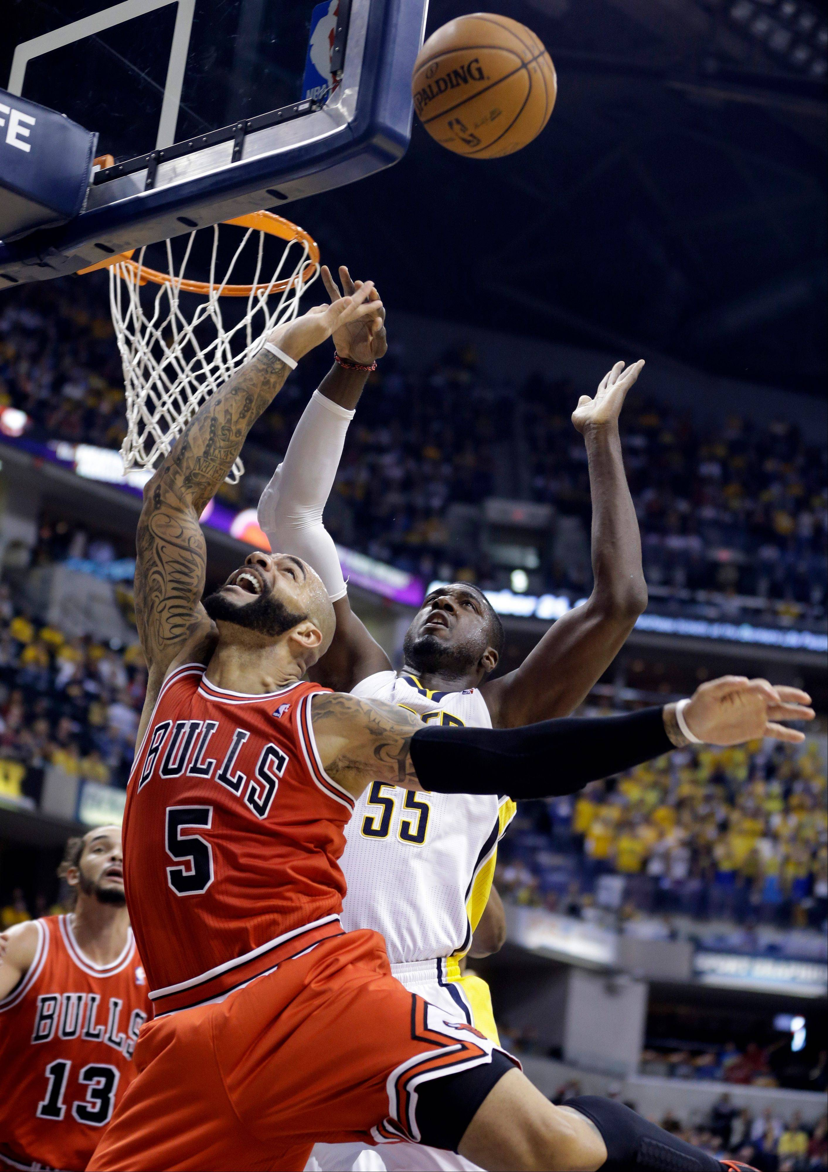 Indiana Pacers center Roy Hibbert comes from behind to block the shot of Chicago Bulls forward Carlos Boozer in the first half of an NBA basketball game in Indianapolis, Wednesday, Nov. 6, 2013. (AP Photo/Michael Conroy)