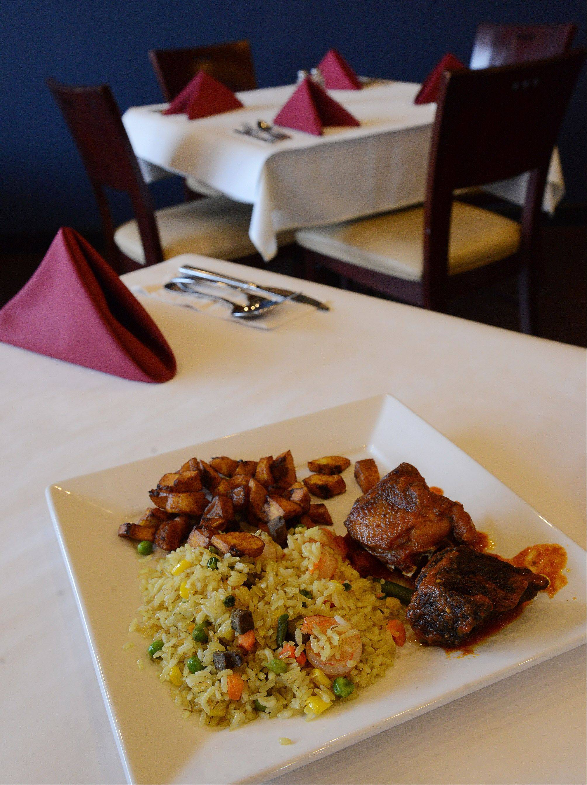 Fried rice with shrimp, beef liver and mixed vegetables, served with beef, chicken and plantains at Bisi African Restaurant in Schaumburg.