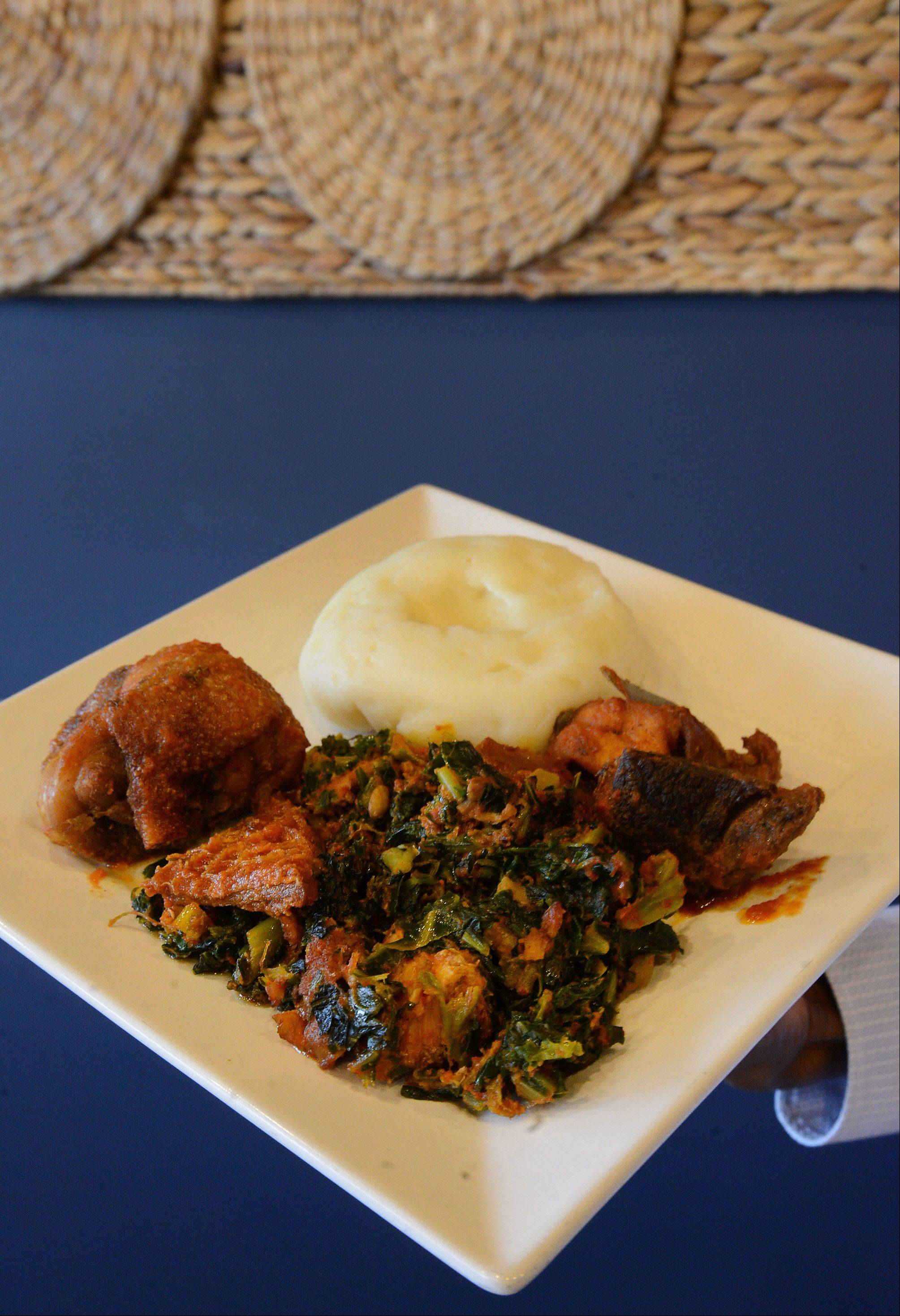 Efo riro, or spinach vegetable soup, is served with chicken and side of fufu, or pounded yam.